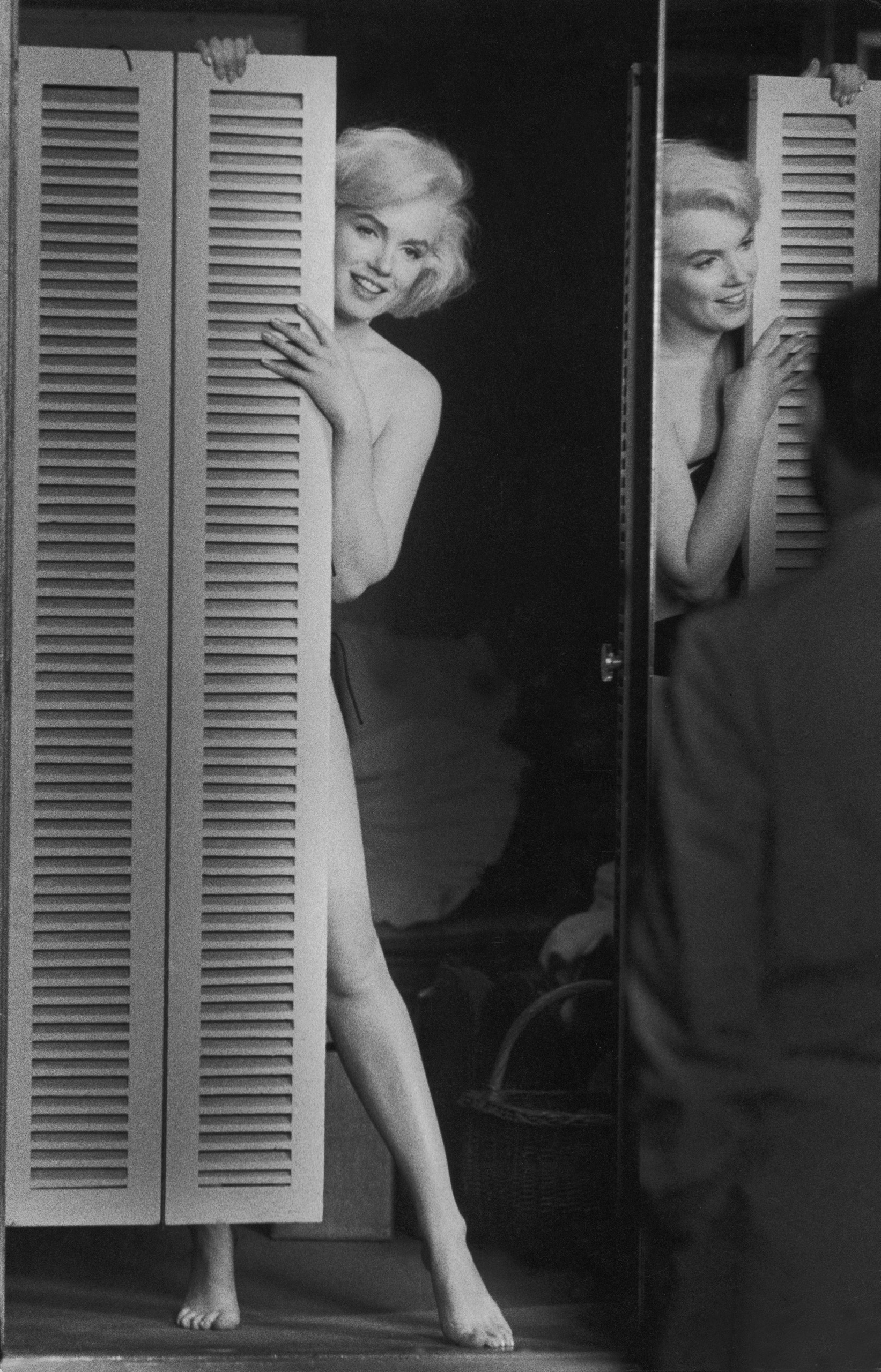Marilyn Monroe peers out at husband Arthur Miller from behind a door to see if he approves, 1960.