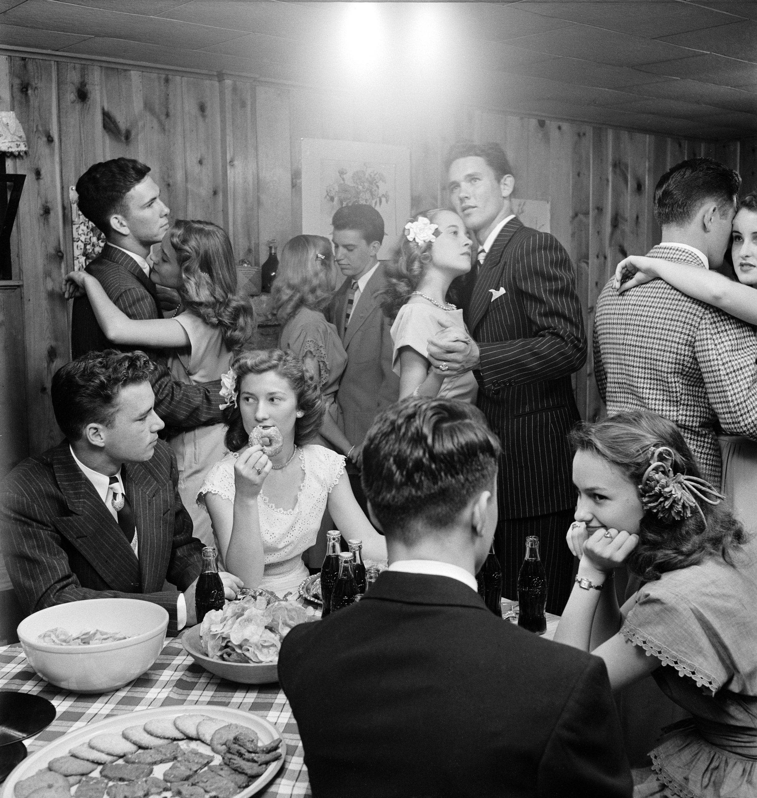 <b>Caption from LIFE.</b> At a party, teen-agers of the Bounds twins' set munch doughnuts and sip Cokes whenever they are not dancing with serious faces to sentimental music. At right, Barbara dances with Jimmy Dick.