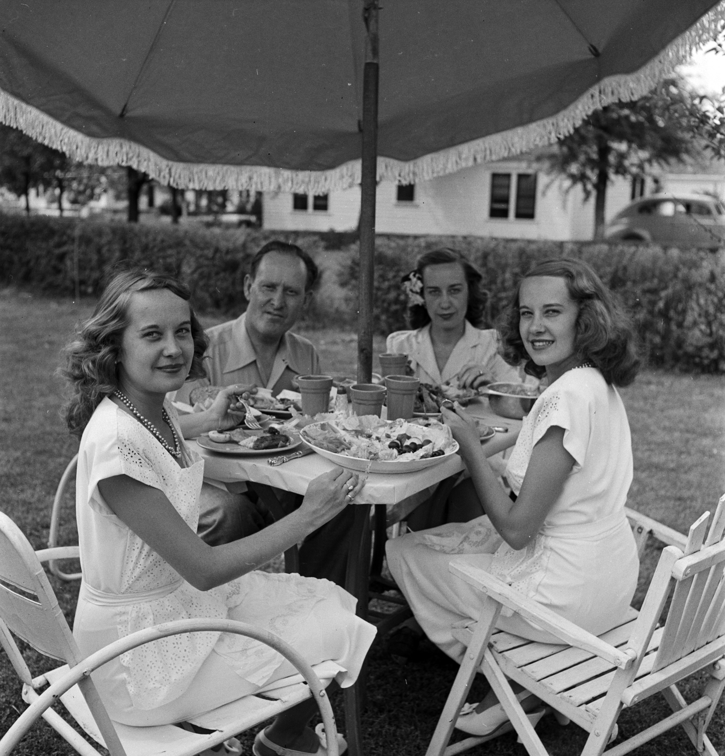 Identical twins Barbara and Betty Bounds eat al fresco with their parents in Tulsa, Okla.