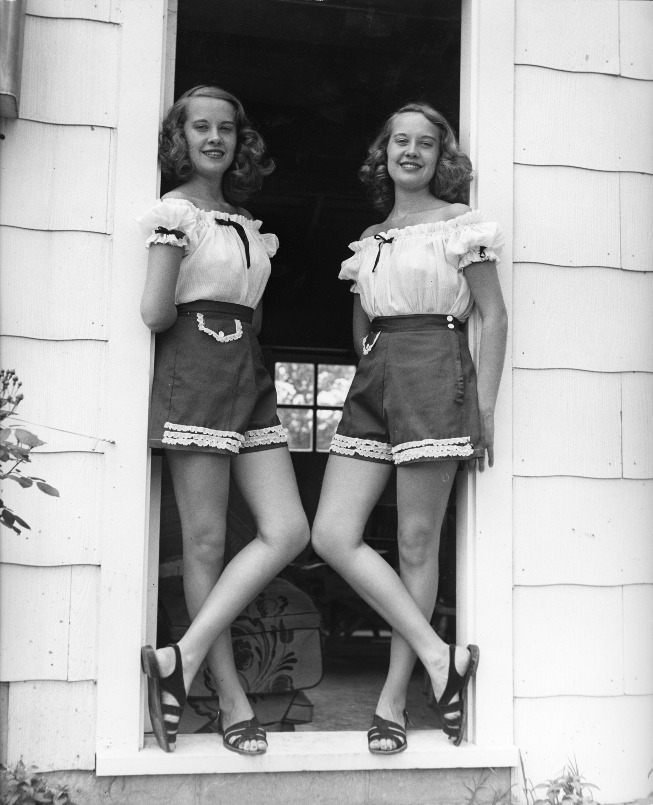 Barbara and Betty Bounds pose in matching outfits, 1947.