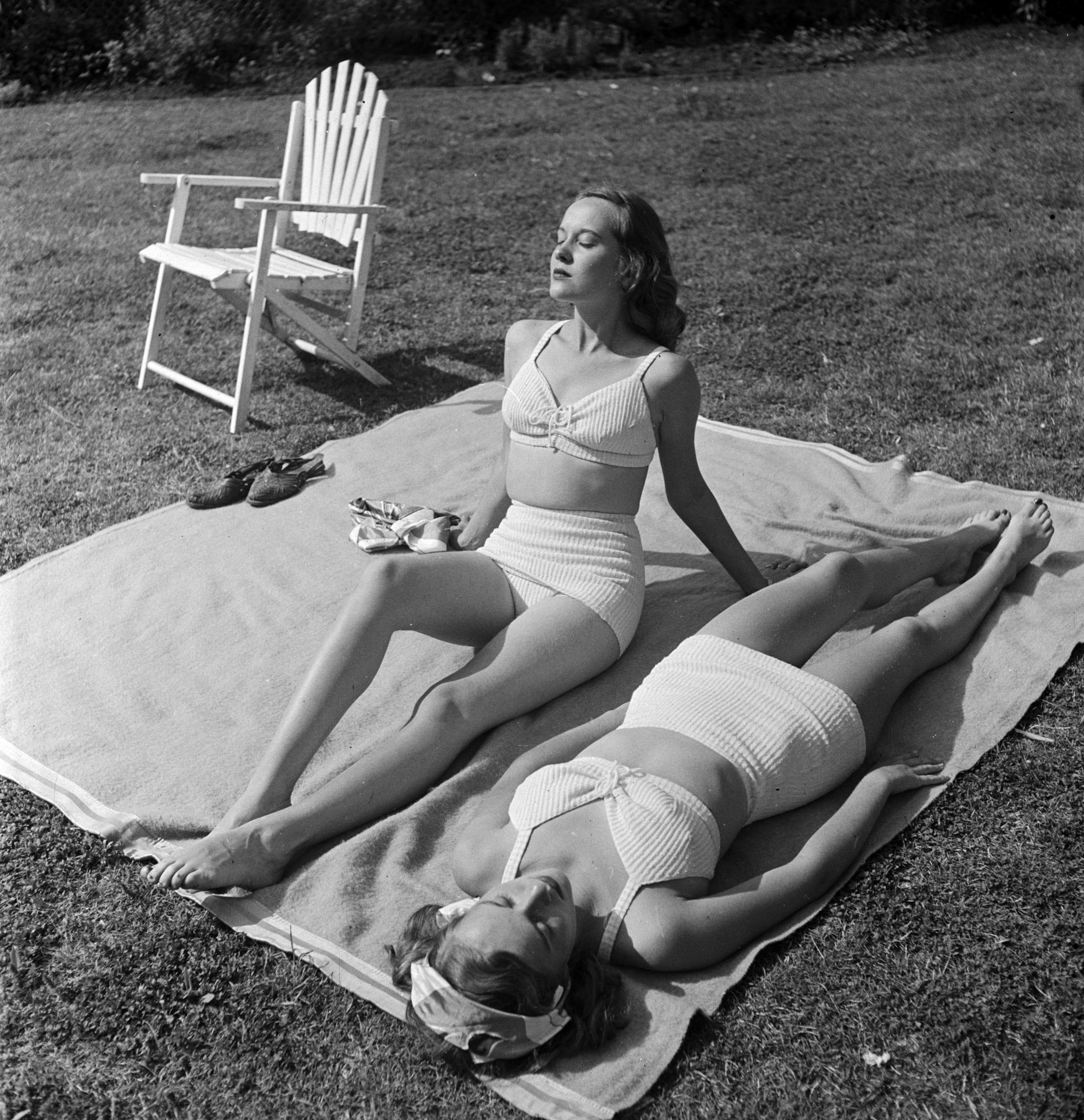 Barbara and Betty Bounds sunbathe side by side.