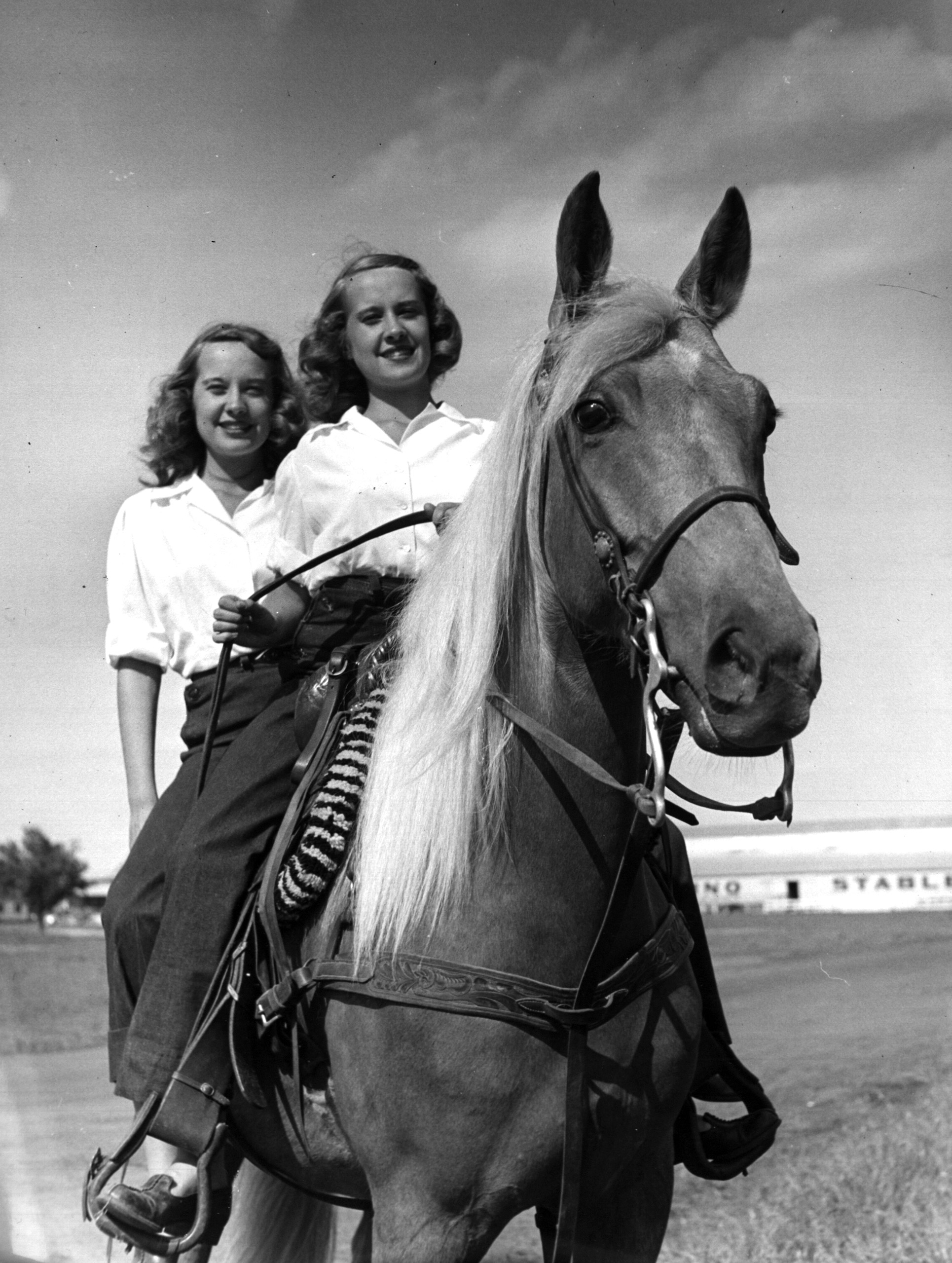 Identical twins Barbara and Betty Bounds ride a horse together.