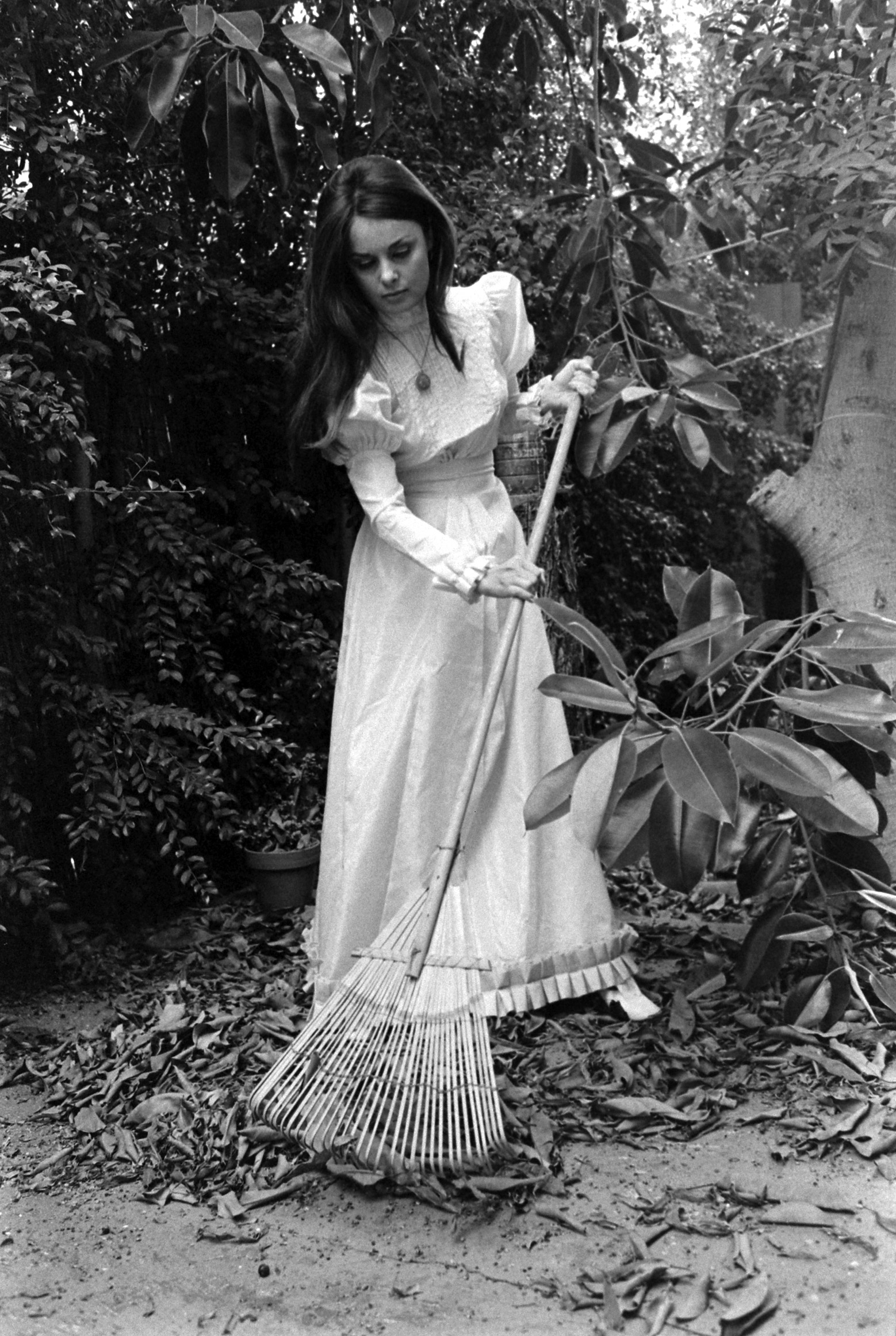 Caption from LIFE. A lady author must: commune with nature. There isn't an awful lot of nature to commune with in Hollywood, but Jeanne does her best with a rake and leaves, both borrowed from her apartement house. The Victorian dress is brand-new.