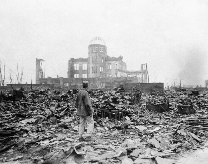 September 8, 1945, an allied correspondent stands in the rubble in front of the shell of a building that once was a movie theater in Hiroshima, Japan, a month after the first atomic bomb ever used in warfare was dropped by the U.S. on Aug. 6, 1945.The damaged building standing in the background is the Hiroshima Prefectural Industrial Promotion Hall, currently preserved as the Atomic Bomb Dome.