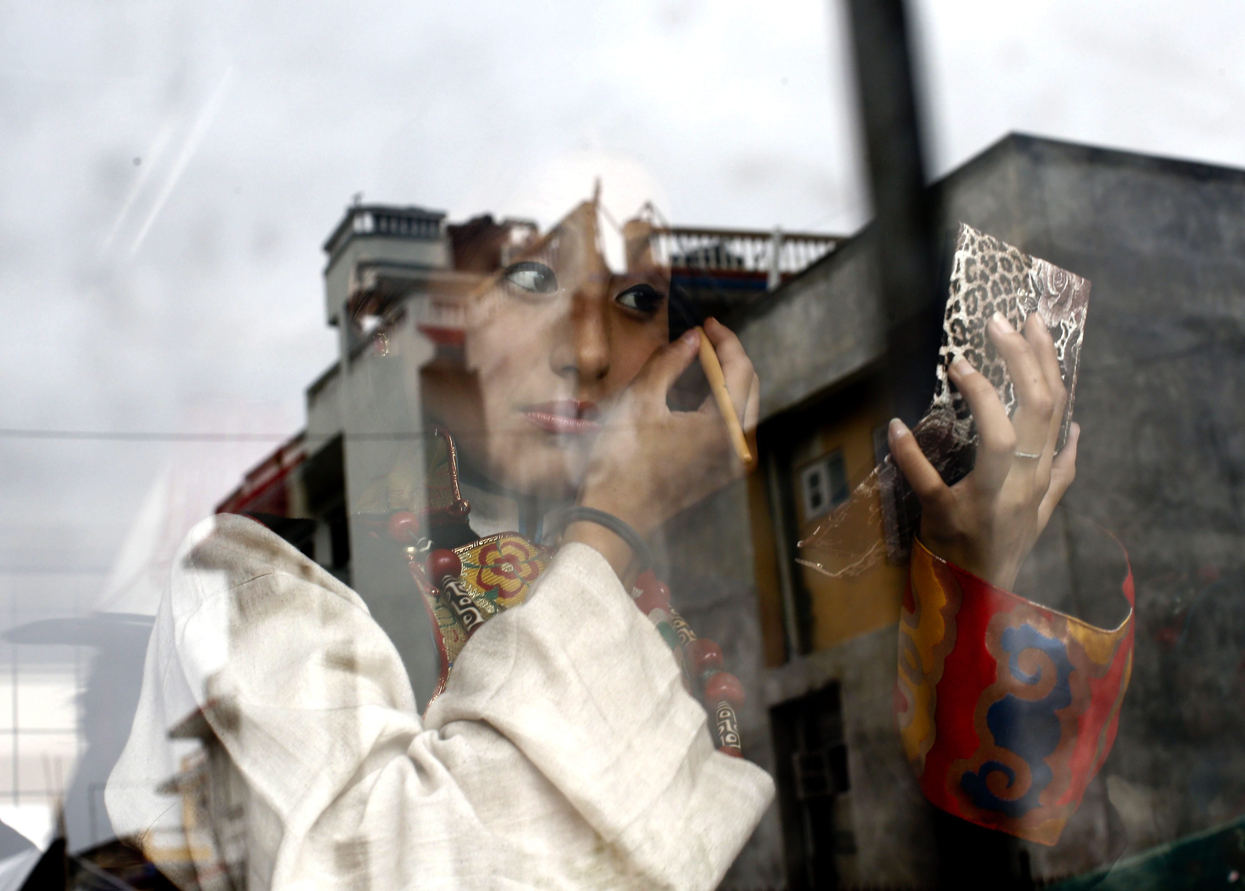 A Tibetan girl puts on make up before the Dalai Lama's 80th birthday at Namgyal School  in Kathmandu on July 6, 2015.