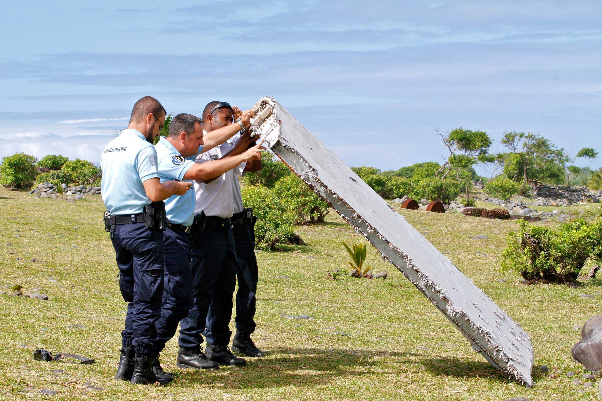 French police officers inspect a piece of debris from a plane in Saint-Andre, Reunion Island, on July 29, 2015.