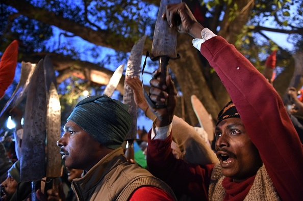 Butchers raise their blades at a temple before the first animal sacrifices by priests are conducted for the Gadhimai festival in the village of Bariyapur, Nepal, on Nov. 28, 2014