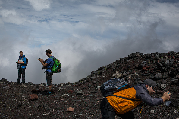Climbers stop to take photographs along a trail to the summit of Mt Fuji on July 2, 2015 in Fujiyoshida, Japan