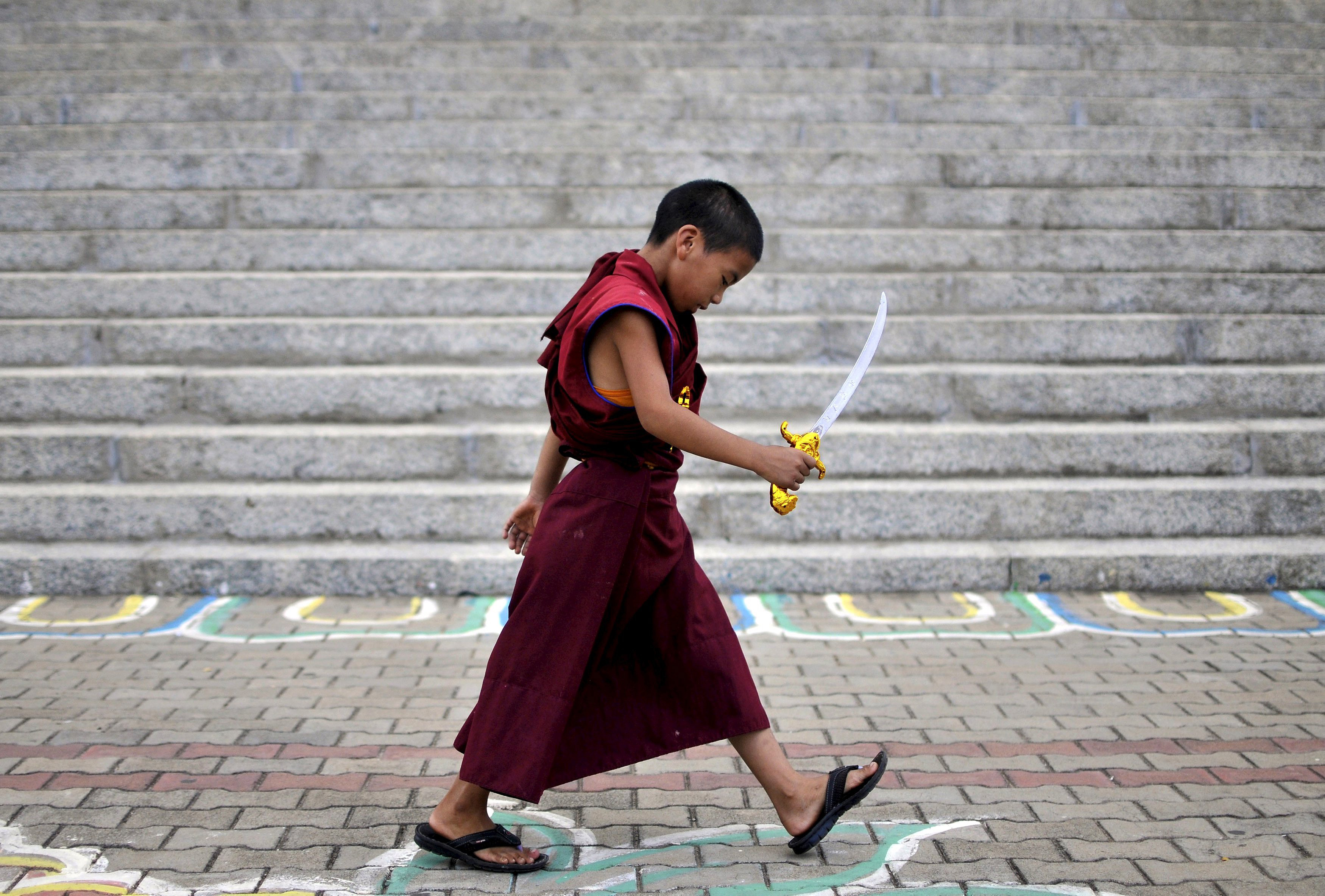 A novice Tibetan monk walks while holding a toy sword as he attends the 80th birthday of the Dalai Lama, at the Sera Jey Monastery in Bylakuppe in the southern state of Karnataka, India on July 6, 2015.