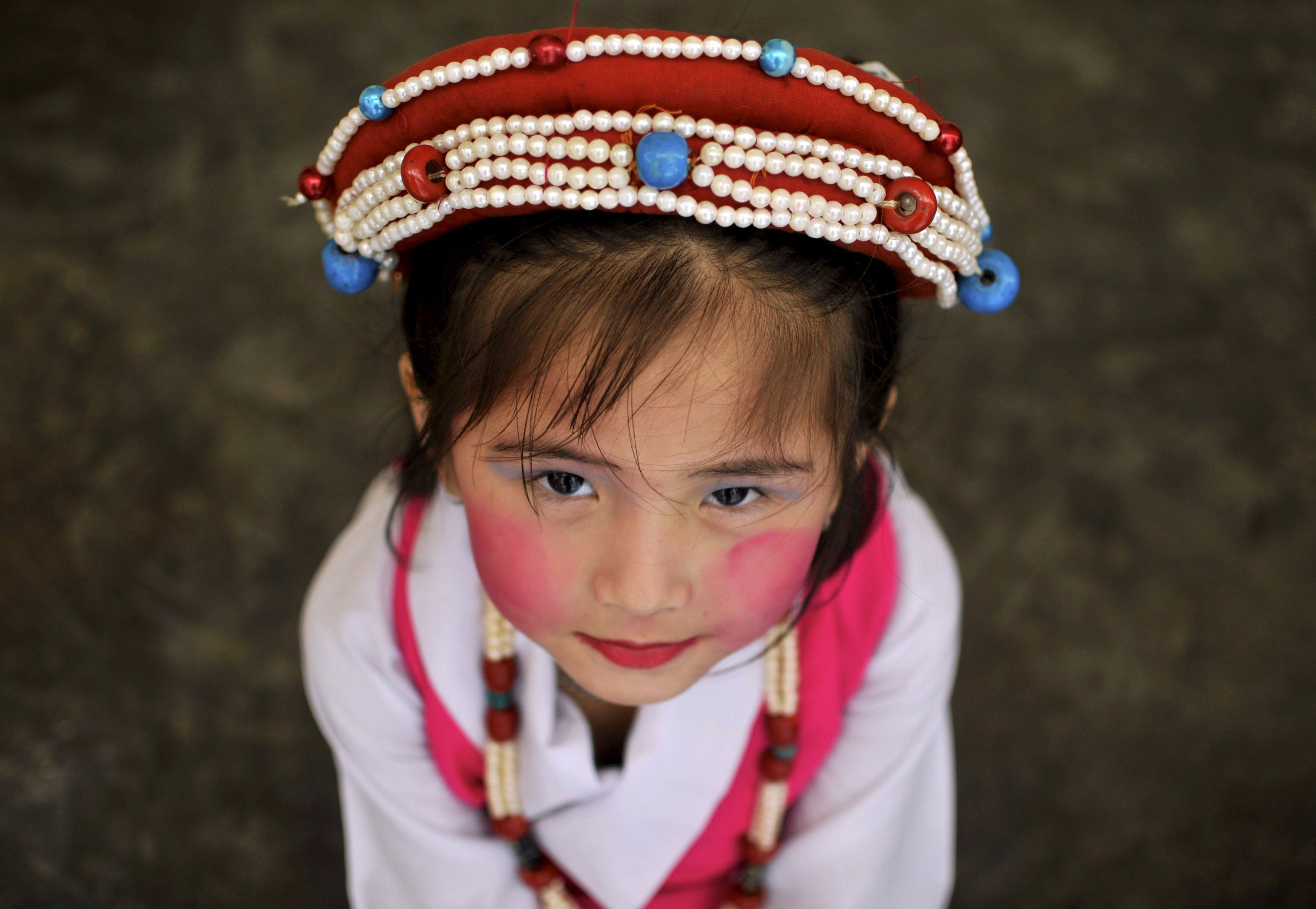 A Tibetan girl in a traditional costume waits backstage before performing at a celebration for the 80th birthday of the Dalai Lama, at the Sera Jey Monastery in Bylakuppe in the southern state of Karnataka, India on July 6, 2015.