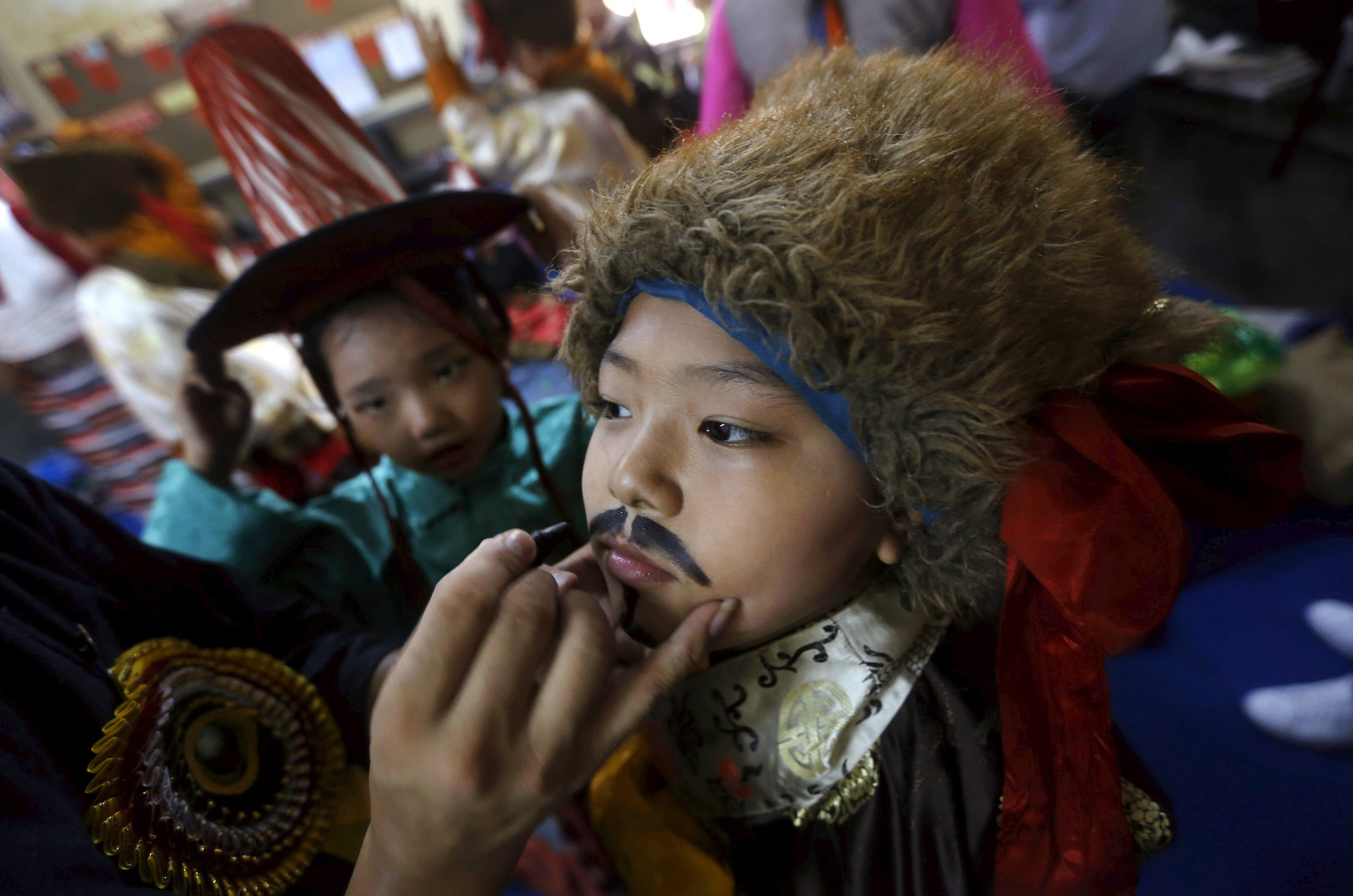 A young Tibetan exile has make-up applied on his face as he gets ready to perform for the Dalai Lama's 80th birthday, at Majnu Ka Tila, a Tibetan refugee camp in New Delhi, India on July 6, 2015.