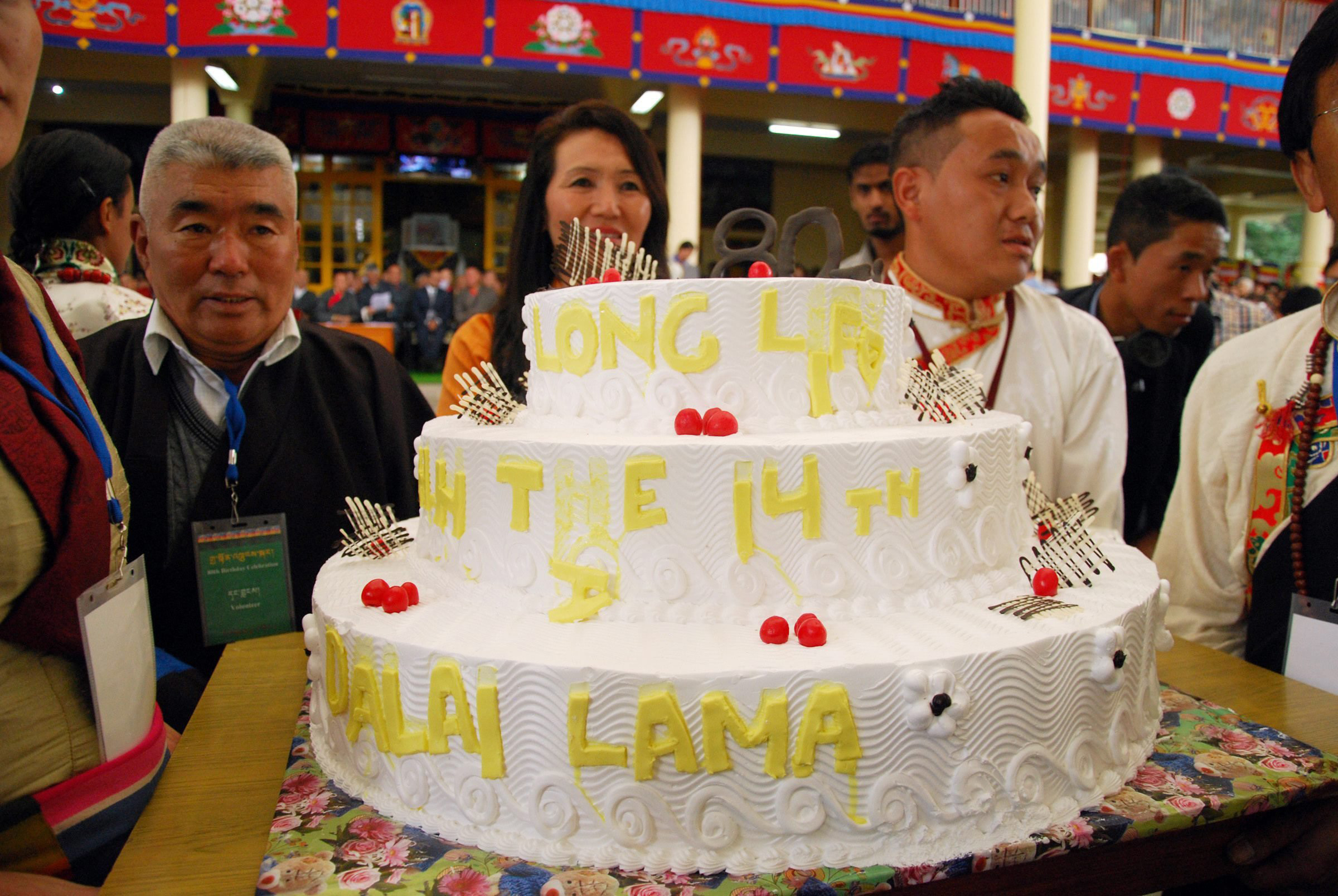 Tibetans living-in-exile in India, stand next to a birthday cake as they celebrate the Dalai Lama's 80th birthday in Dharmsala, India on July 6, 2015.