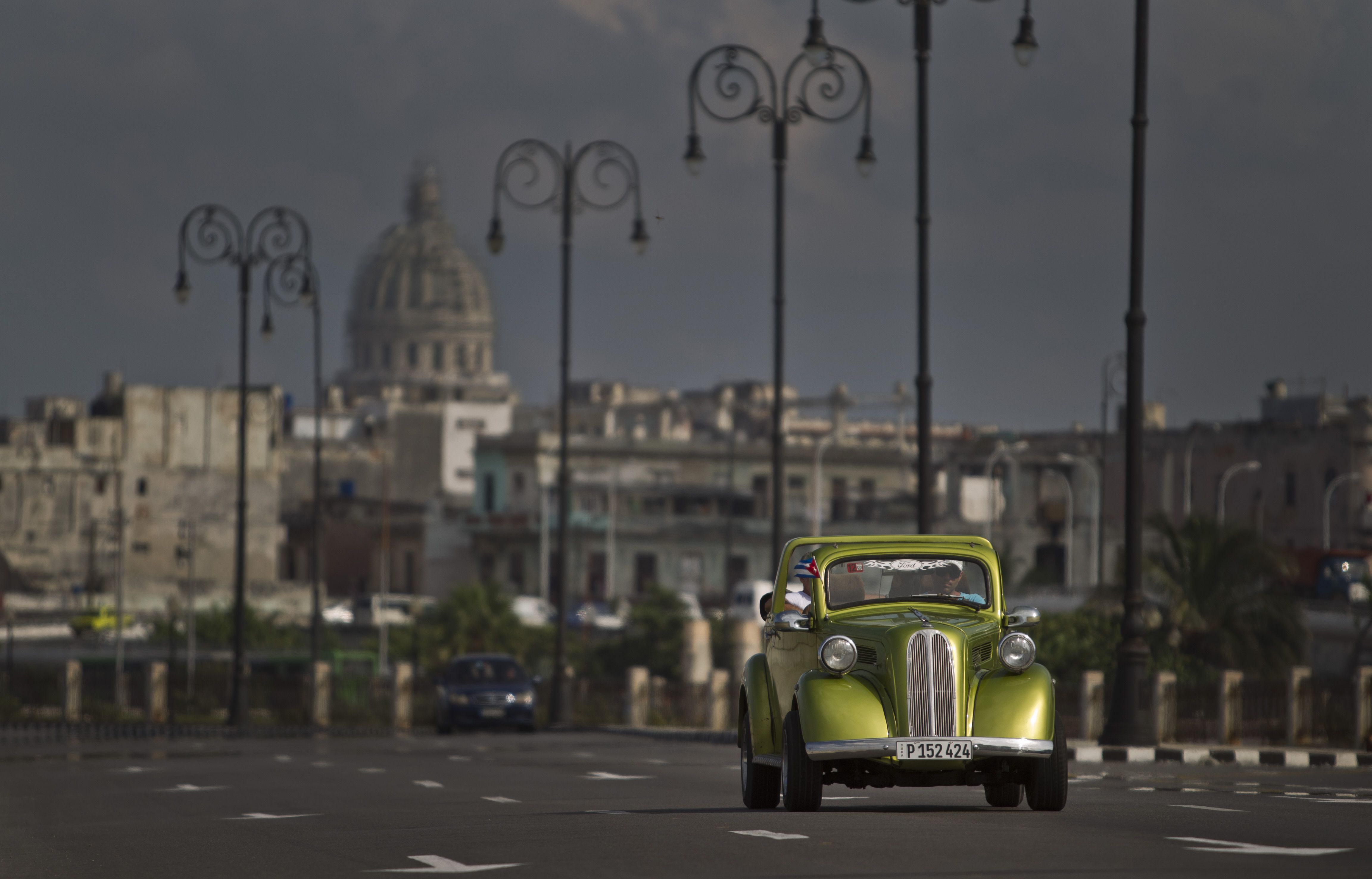 A man drives a classic American car on The Malecon in Havana, Cuba.