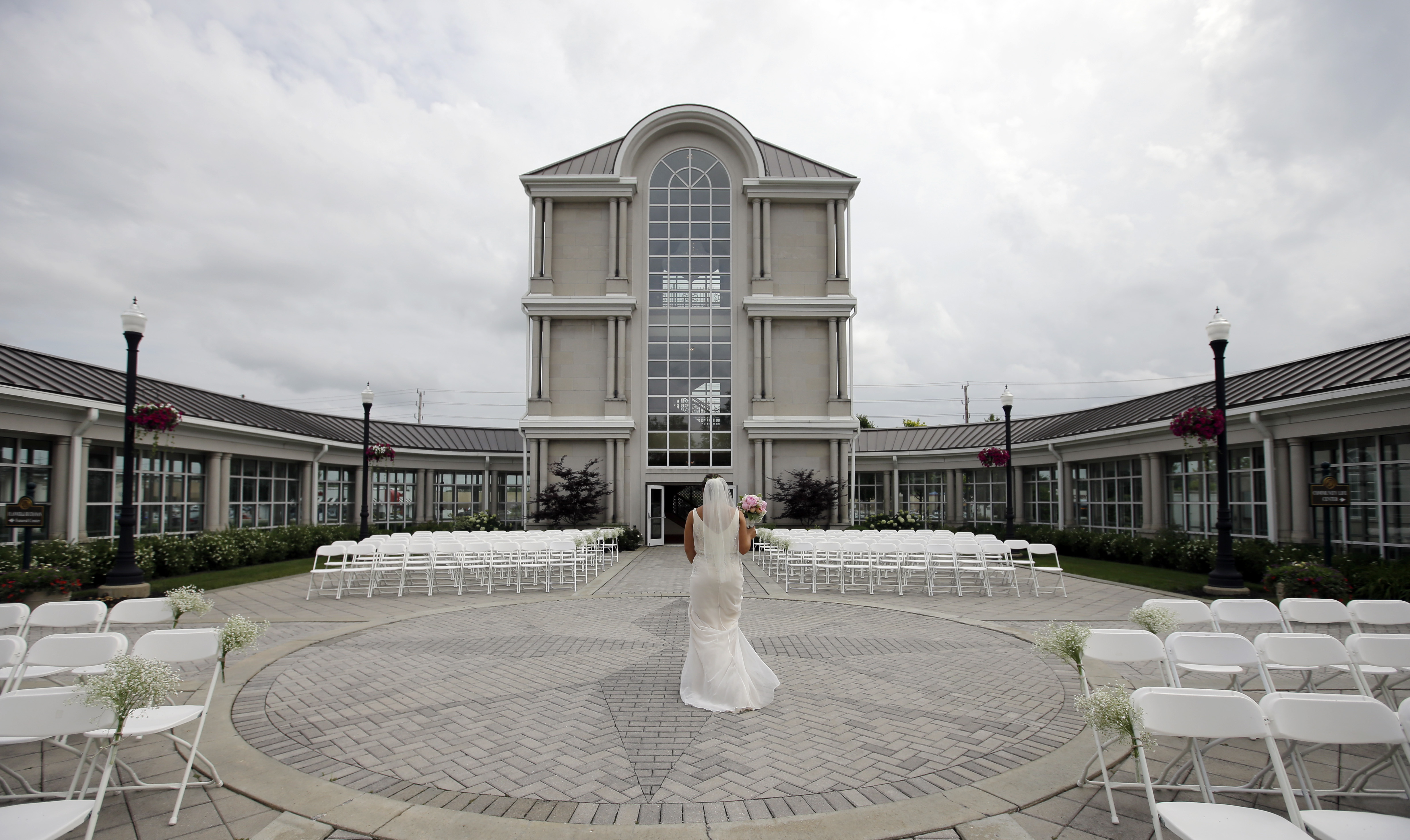 Danessa Molinder walks toward the Crystal Tower for photos before her wedding at the Community Life Center, which sits on cemetery land near a funeral home in Indianapolis.