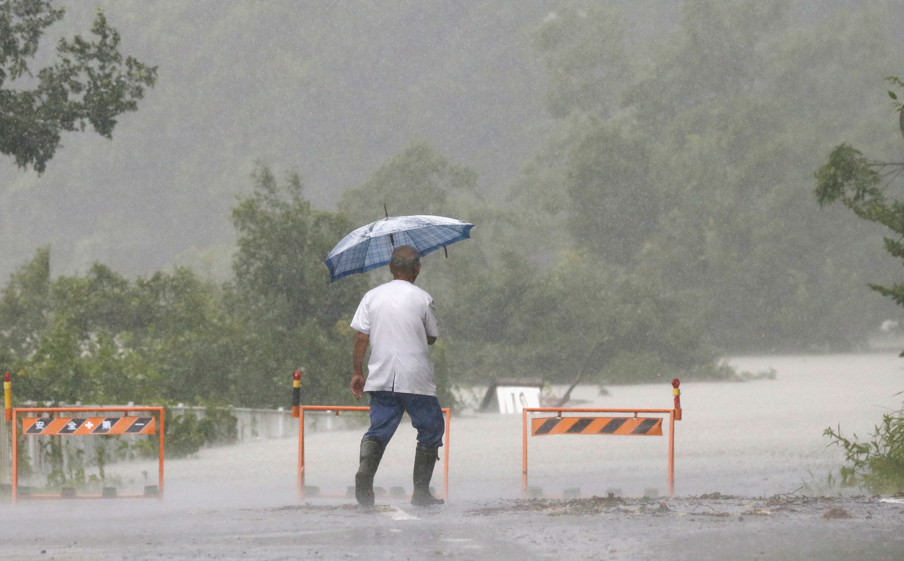 A road in the western Japanese city of Shingu is submerged by water due to an overflowing river on the morning of July 17, 2015, after Typhoon Nangka made landfall in the area the previous day