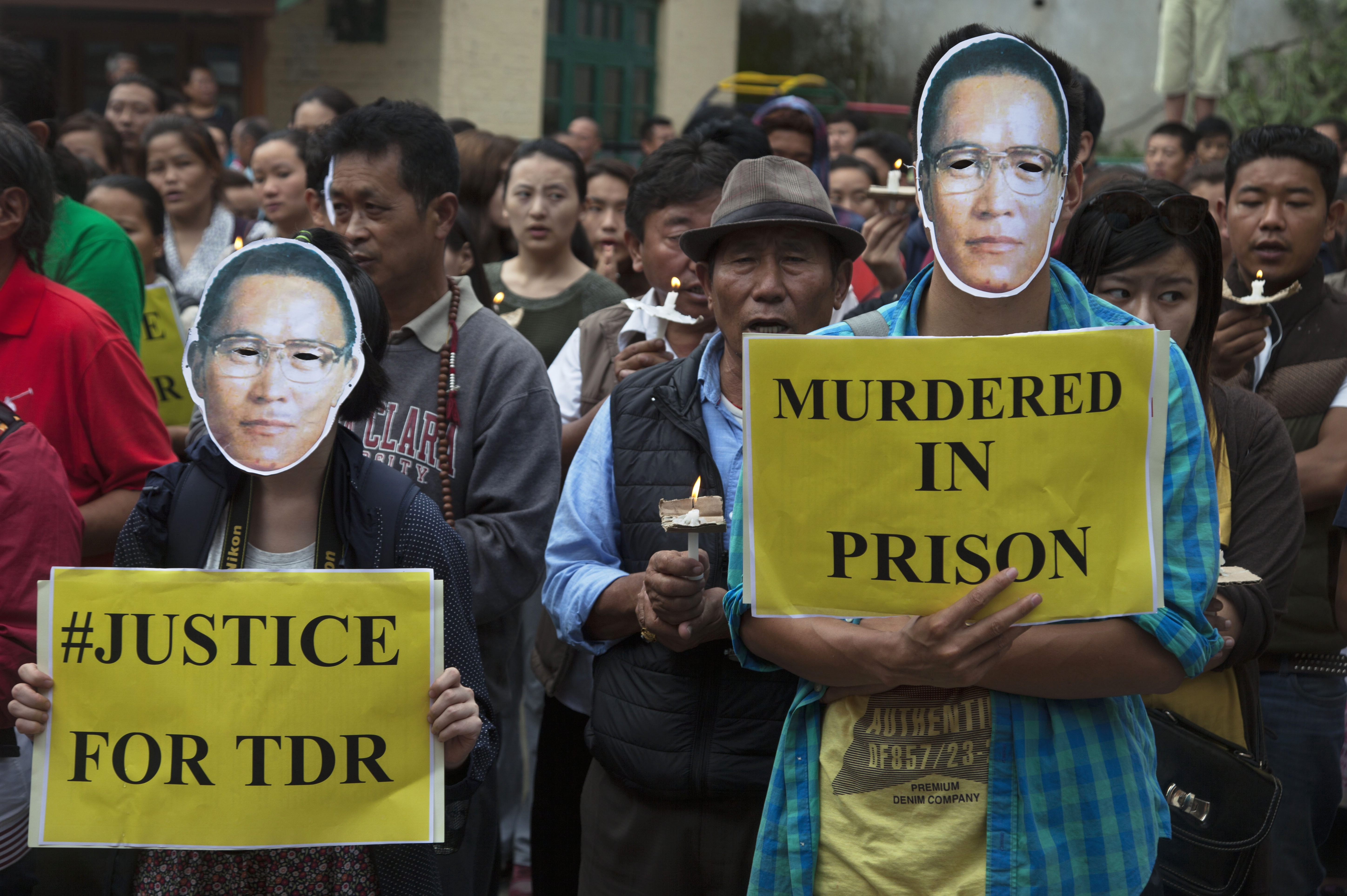 Exiled Tibetans carry placards as they participate in a candlelit vigil to remember Tibetan lama Tenzin Delek Rinpoche in Dharamsala, India, on July 13, 2015