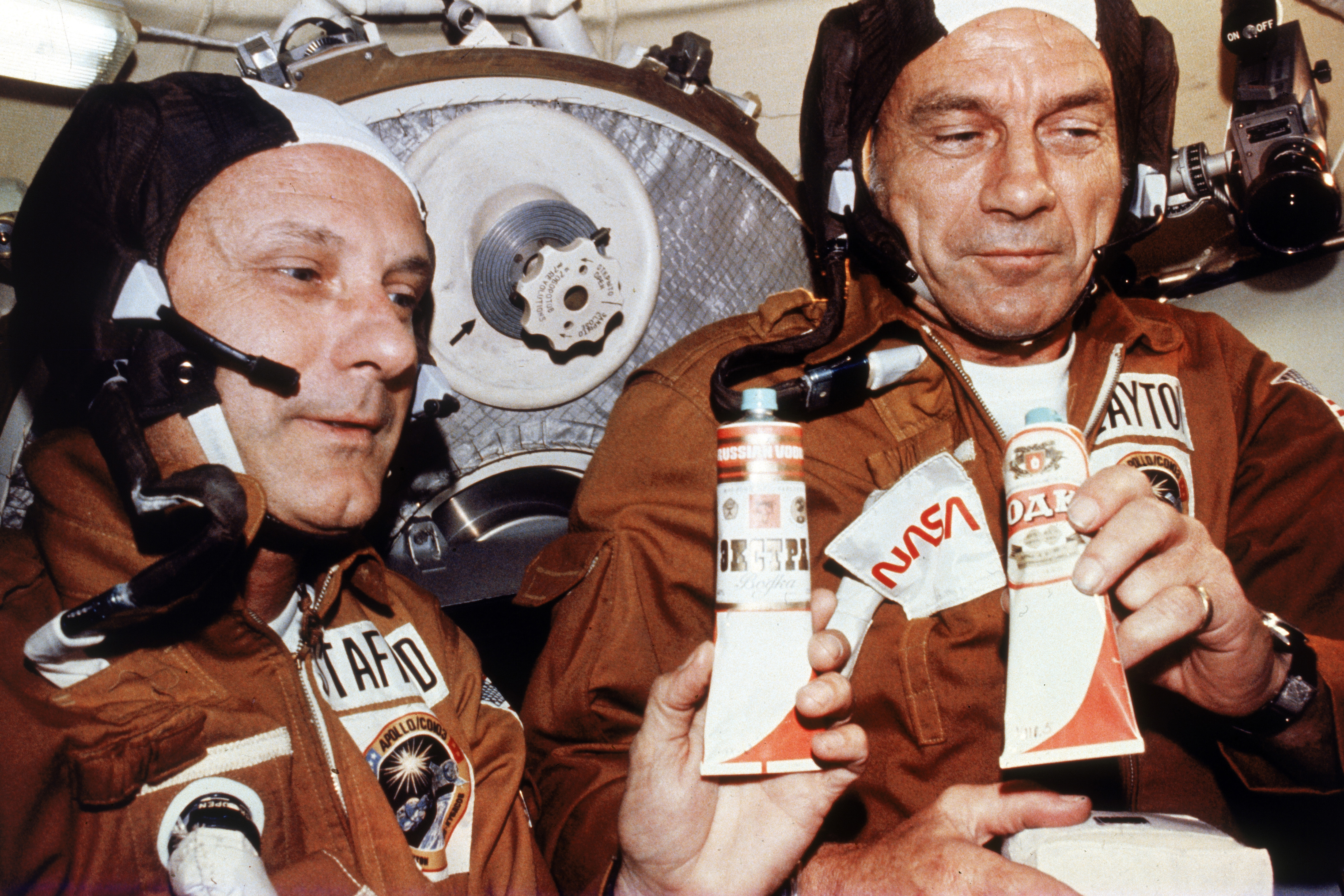American astronauts Tom Stafford and Deke Slayton hold tubes of vodka given to them by Russian cosmonauts during their historic rendezvous and linkup of Apollo and Soyuz spacecraft.