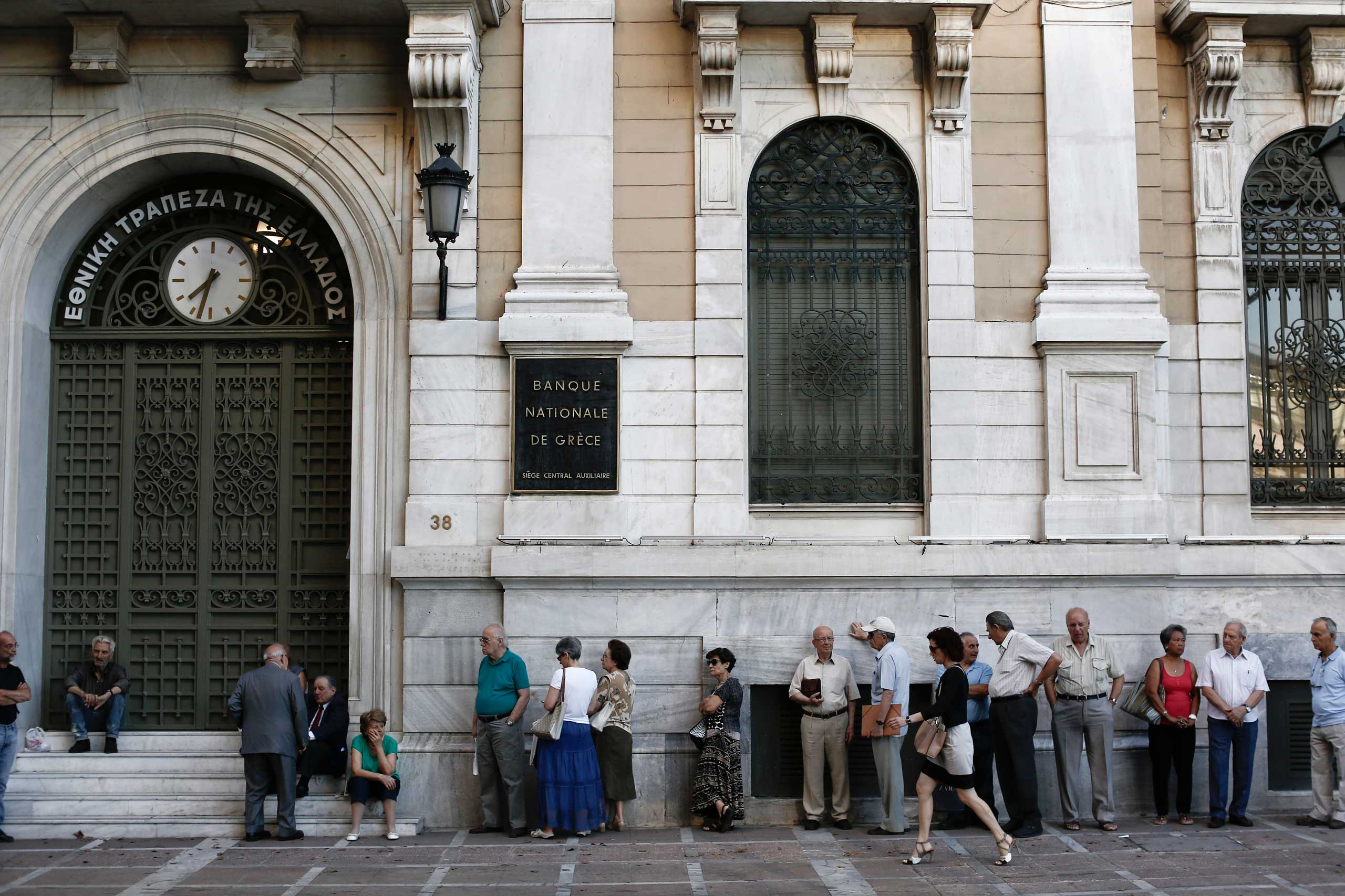 Customers queue outside a National Bank of Greece SA bank branch ahead of opening in Athens, July 20, 2015.