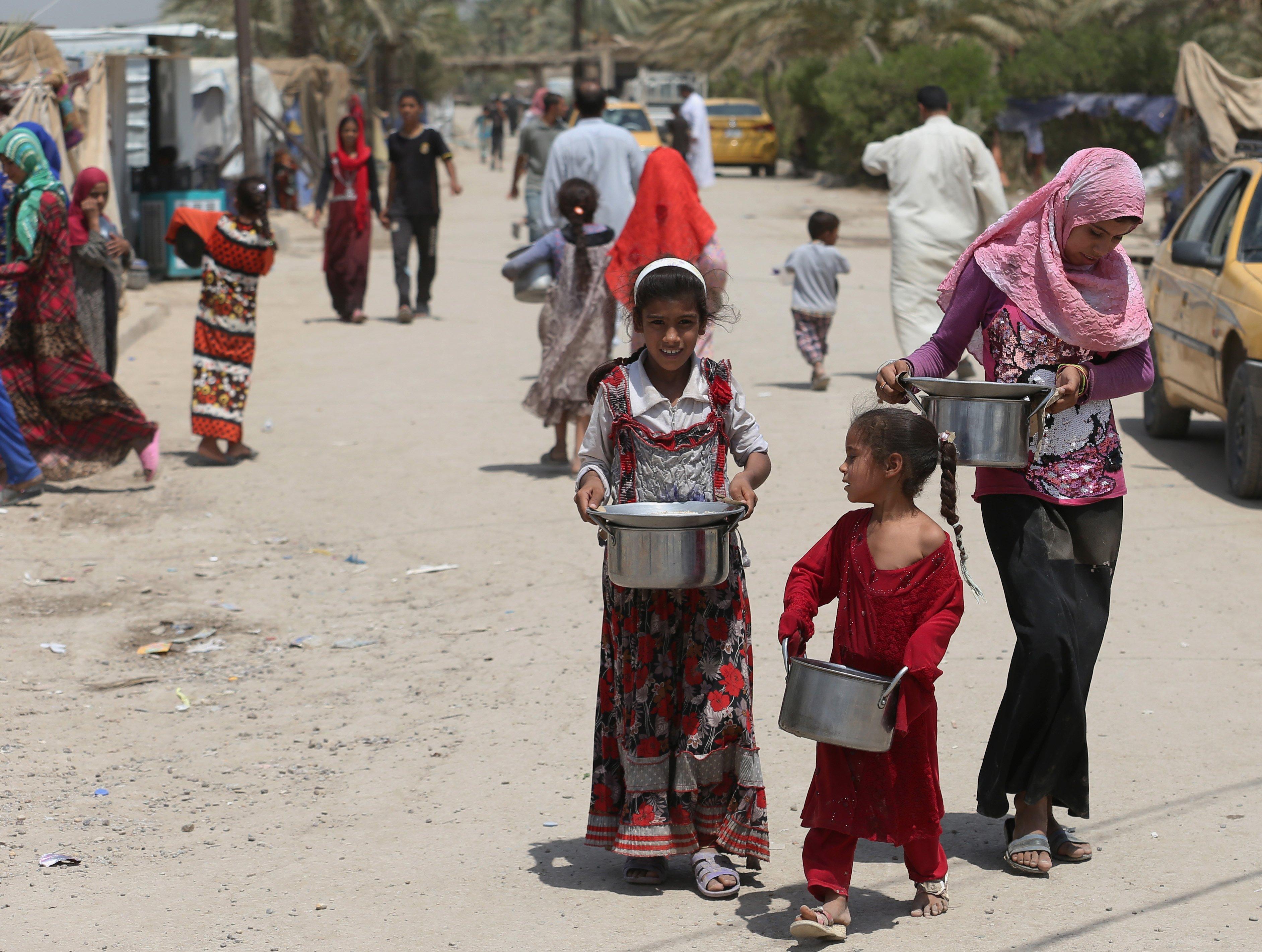 Displaced Iraqis carry donated food at al-Takia refugee camp in Baghdad on July 30, 2015.
