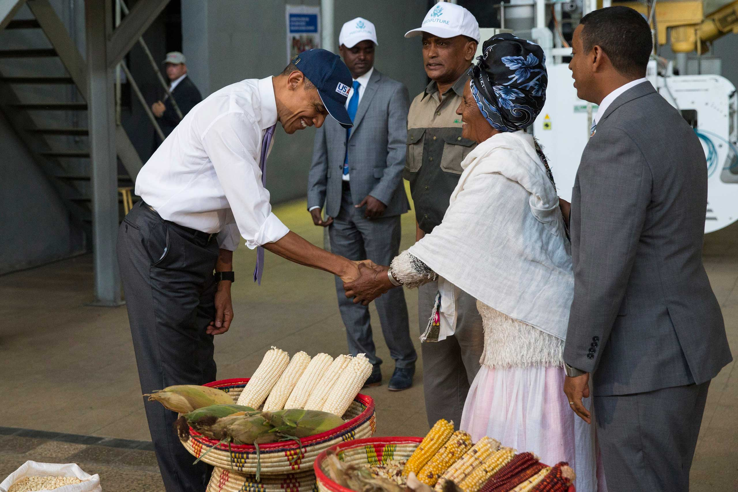 President Barack Obama shakes hands with farmer Gifty Jemal Hussein, after seeing her corn during a tour of Faffa Food in Addis Ababa on July 28, 2015.