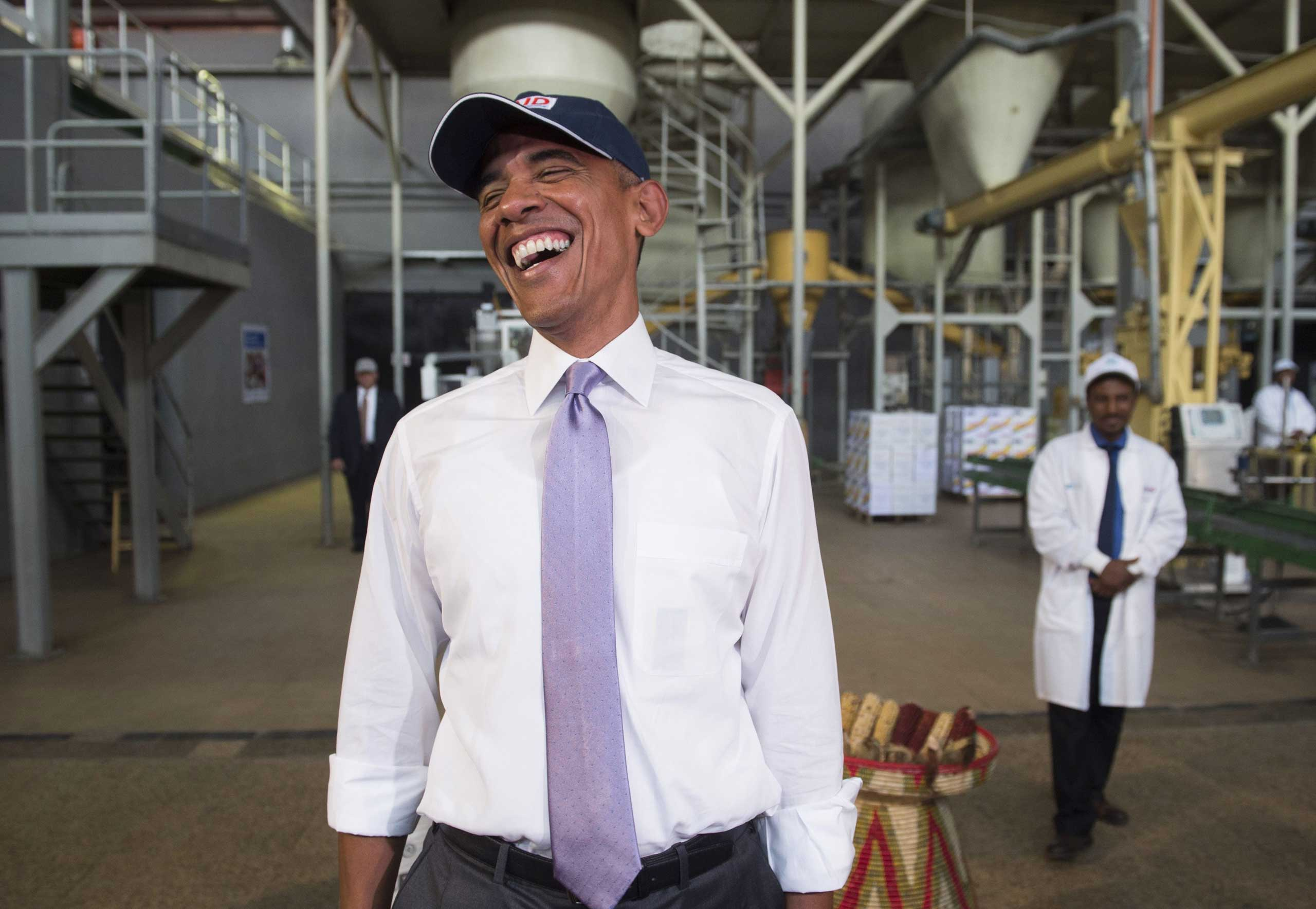 President Barack Obama laughs at the hair nets the members of the press have to wear during a tour of Faffa Food, in Addis Ababa on July 28, 2015.