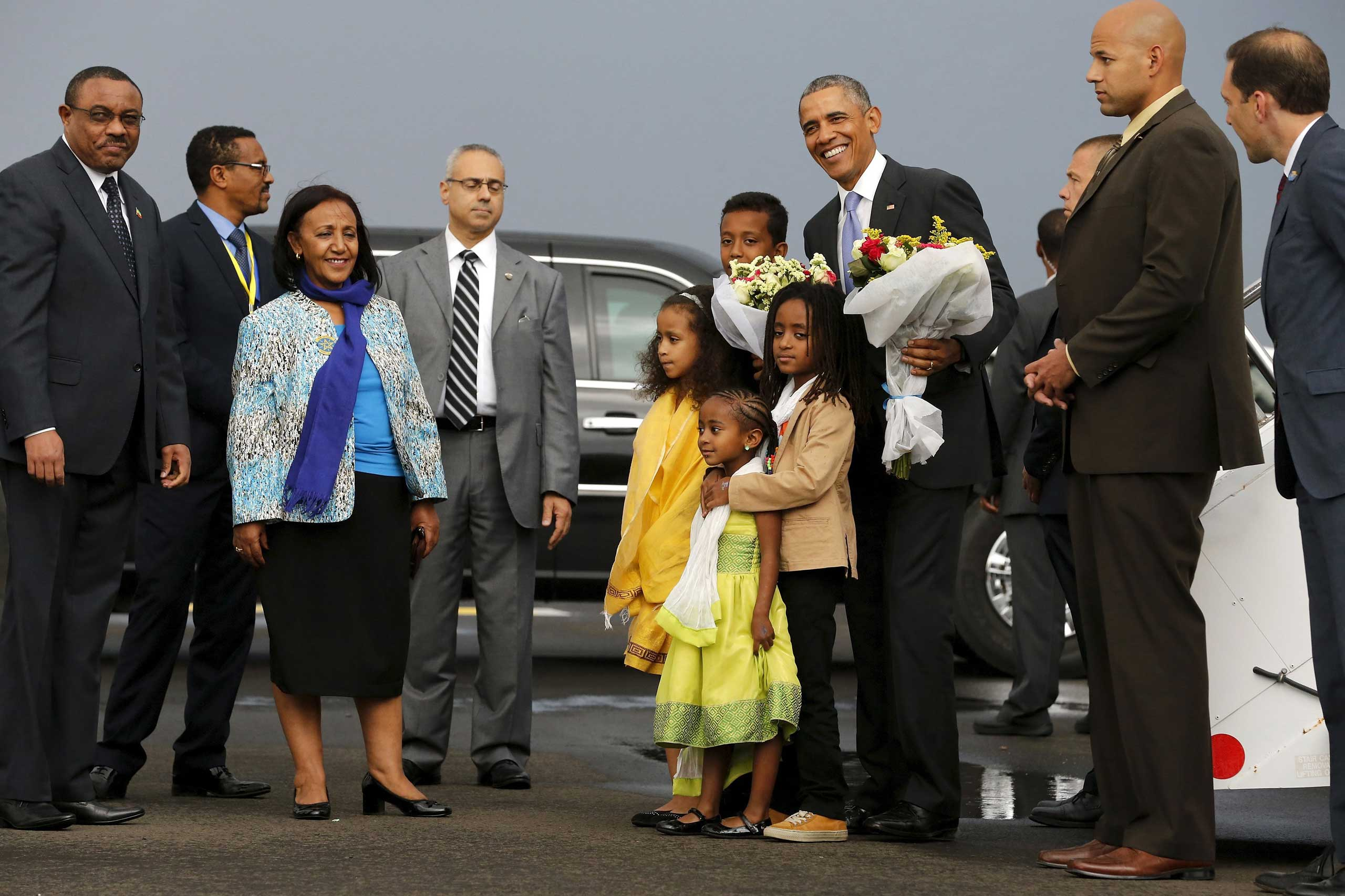 President Barack Obama receives flowers from children, with Ethiopia's Prime Minister Hailemariam Desalegn, as he arrives at Bole International Airport in Addis Ababa on July 26, 2015.