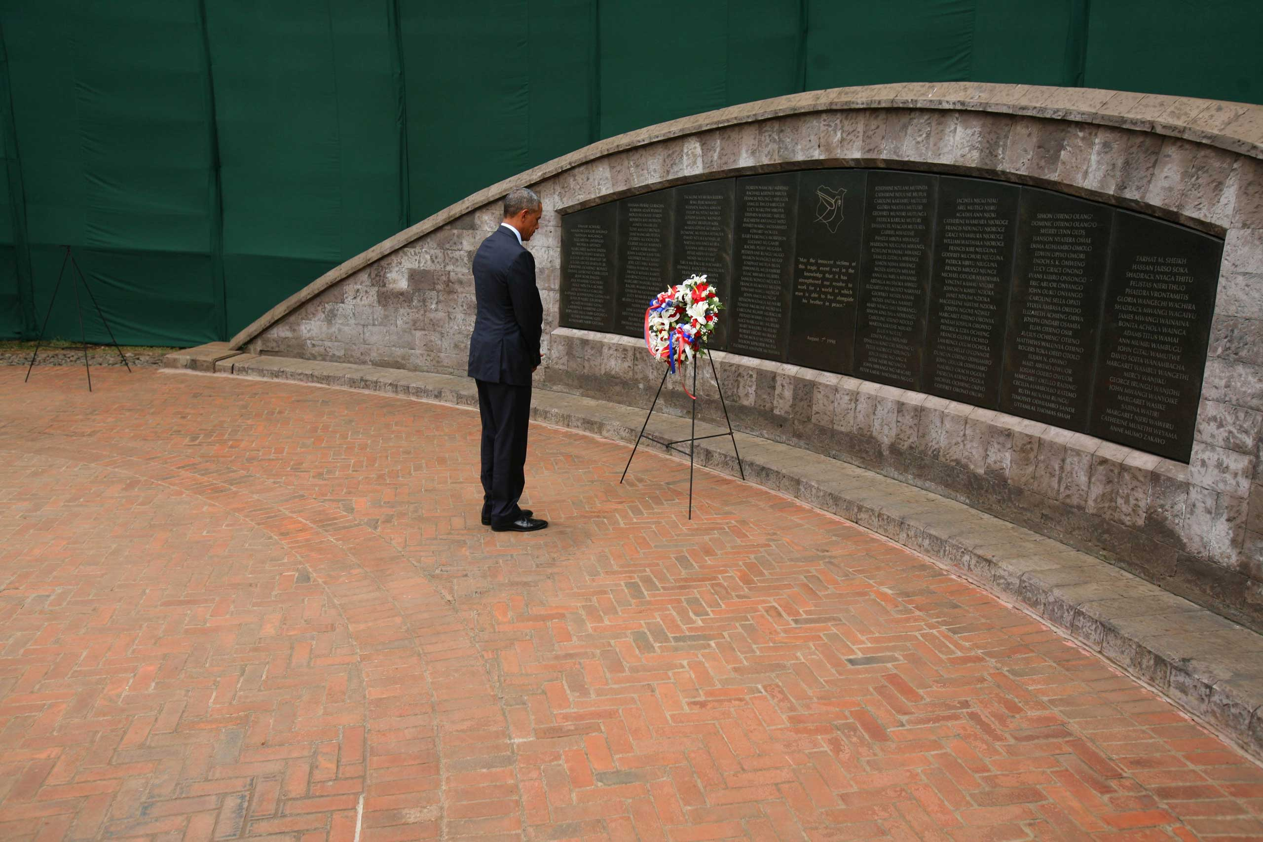 President Barack Obama stands in silent tribute after laying a wreath at the August 7th Memorial Park to pay tribute to the victims of the 1998 bombing at U.S. Embassy in Nairobi, on July 25, 2015.