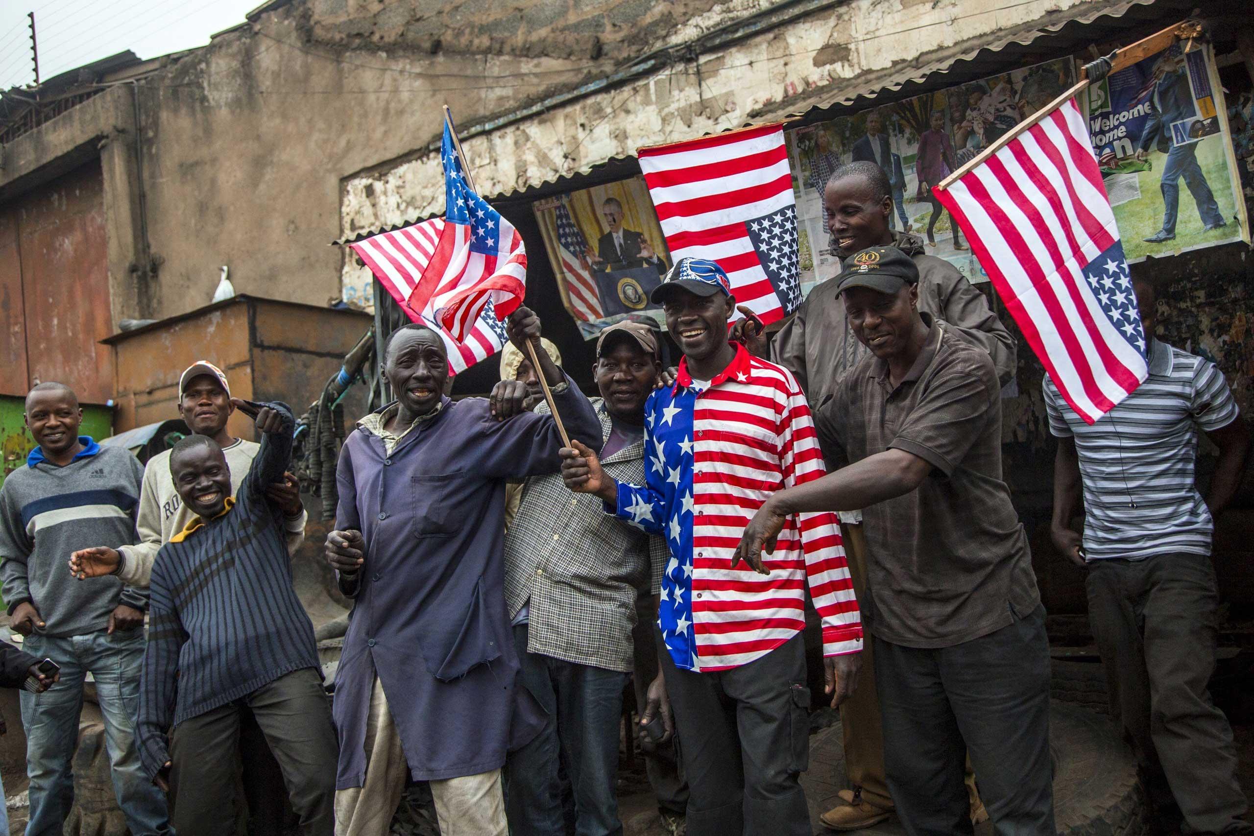 People wave U.S. flags before President Barack Obama's motorcade arrival, in Nairobi on July 25, 2015.