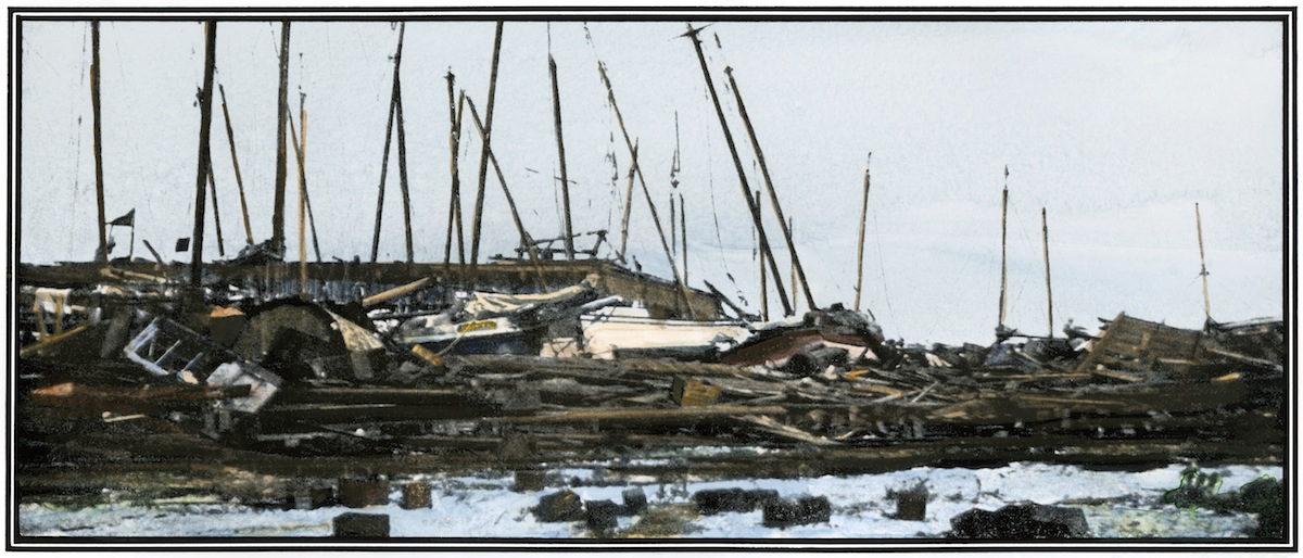 Hand-colored halftone reproduction of a photograph of oyster boats piled up at a Galveston wharf after the hurricane of 1900