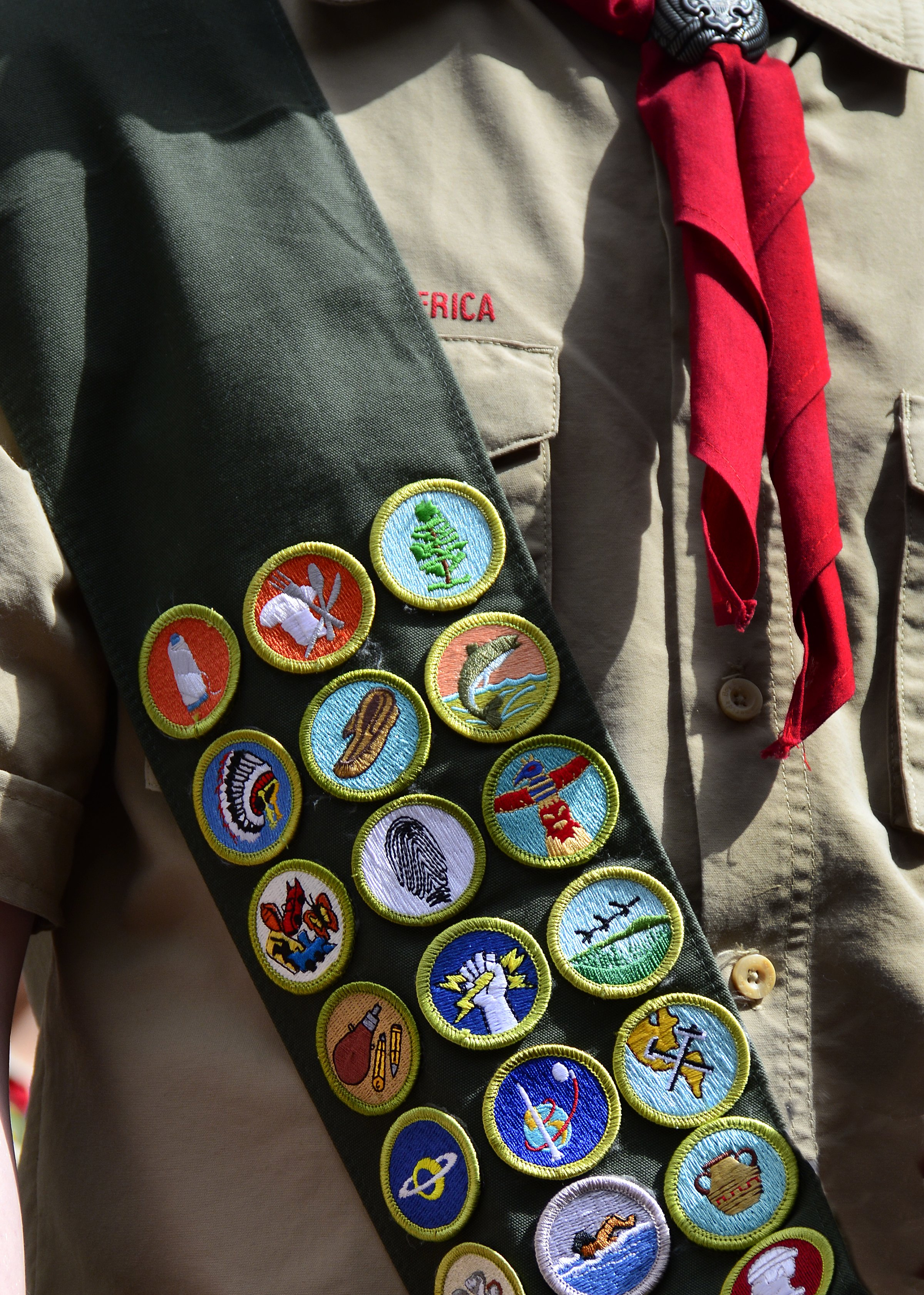 A Boy Scout wears a sash displaying his earned merit badges at a ceremony in New York City. The merit badge sash is worn by a Boy Scout during formal activities and events and not during Troop meetings or campouts.