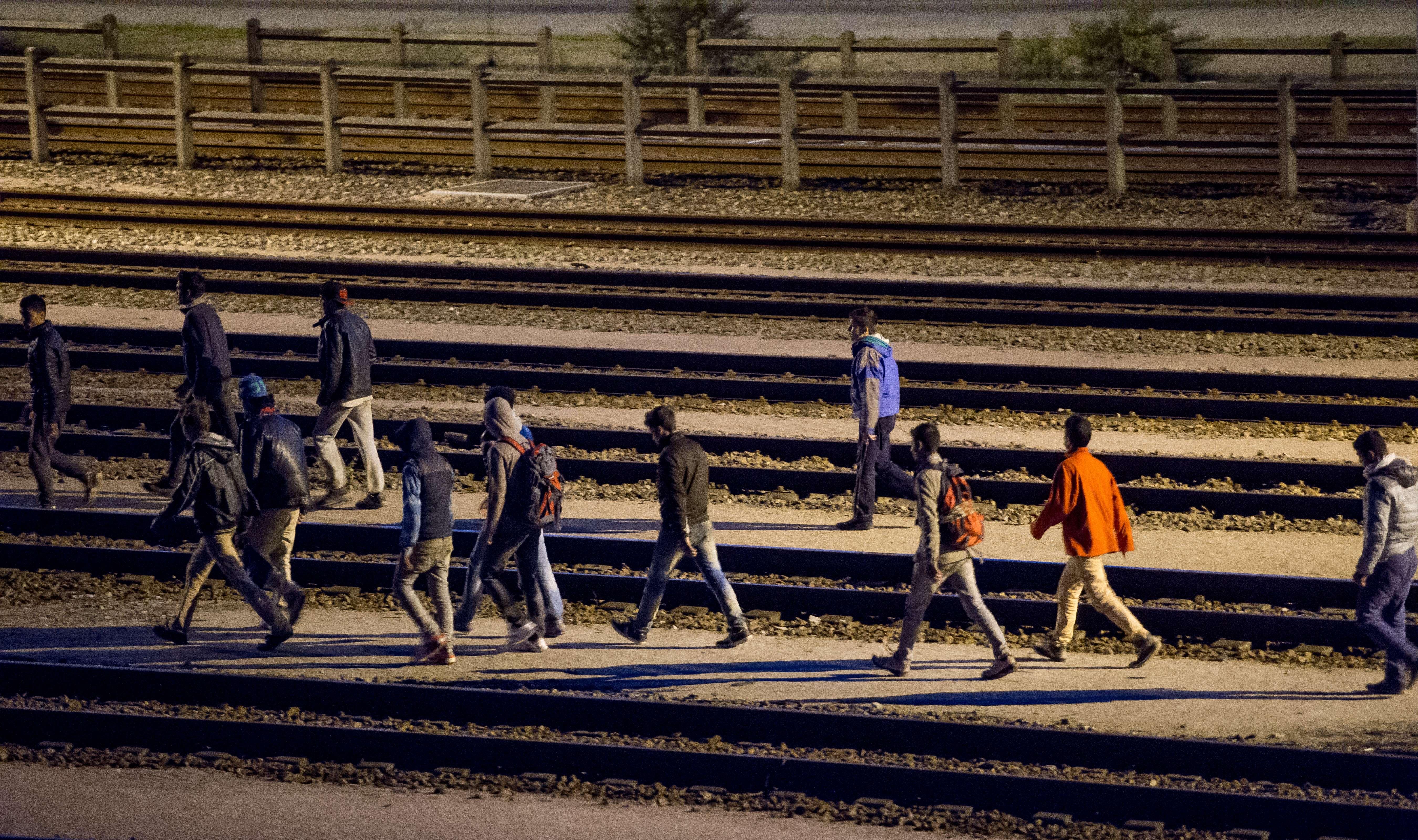 Migrants walk along railway tracks at the Eurotunnel terminal on July 28, 2015, in Calais-Fréthun.
