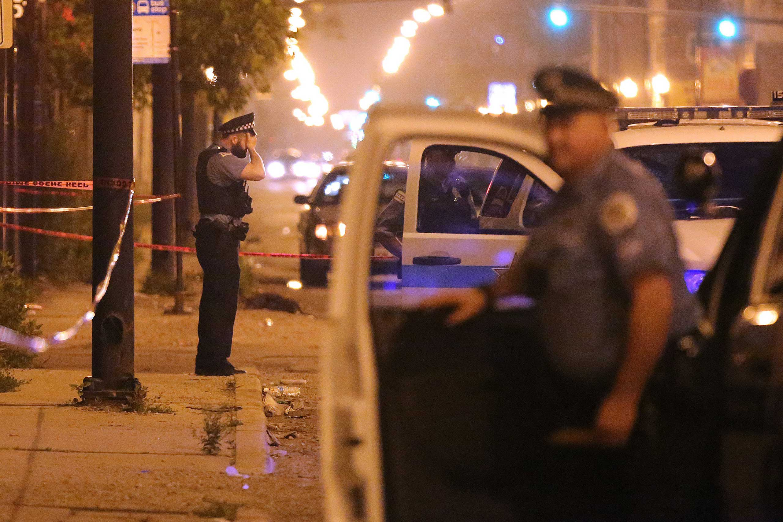 A police officer rests his hand on his forehead at the scene where a 23-year old man was shot in the early morning hours of July 6, 2015 in Chicago.