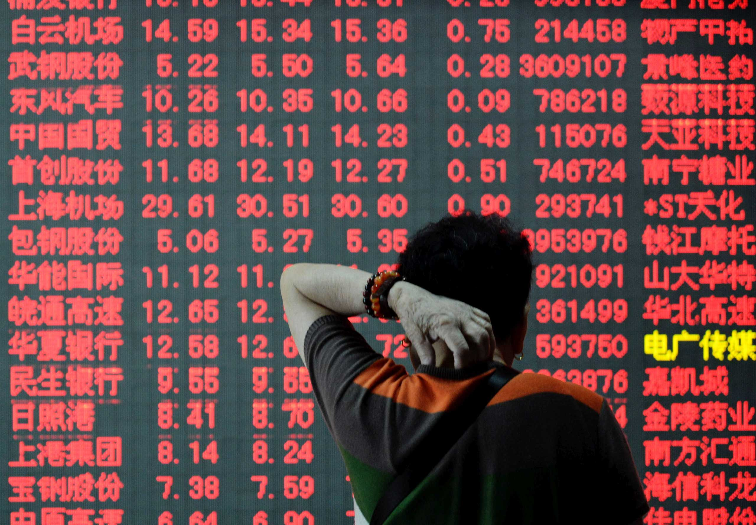 A Chinese investor looks at prices of shares  at a stock brokerage house in Hangzhou city, China on July 23, 2015.