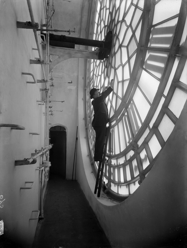 A view of the space behind one of the glass faces of Big Ben, in the clock tower at the Palace of Westminster, London, with a man inspecting repairs.