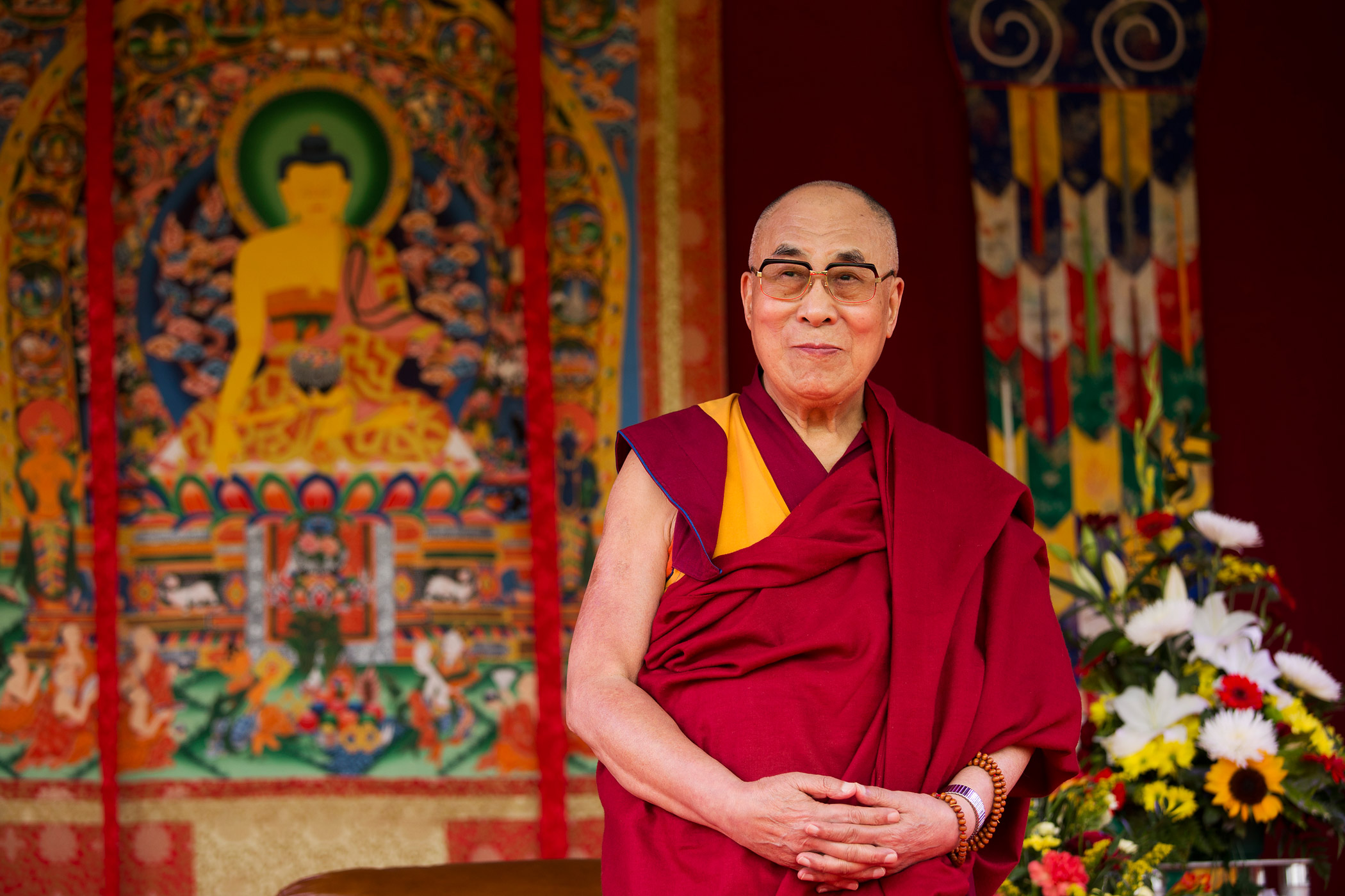 The Dalai Lama stands on stage before making a speech to an audience at the ESS Stadium in Aldershot, England, on June 29, 2015