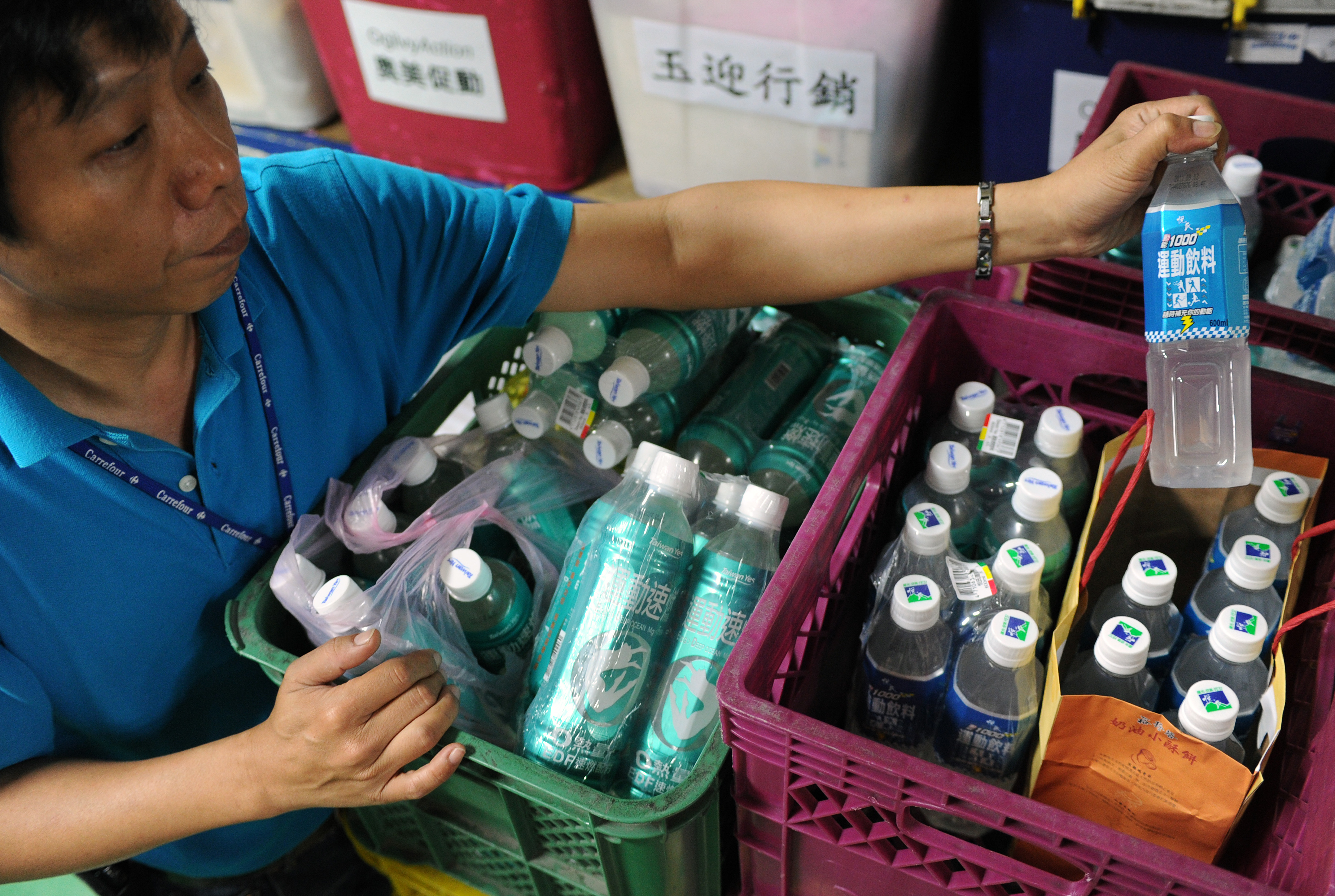 A worker displays a sports drinks containing a platicizer called DEHP after removing at a supermarket in Taiwan in 2011.