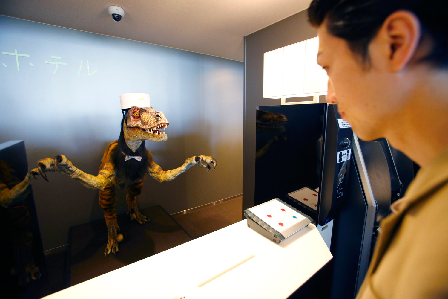 A receptionist dinosaur robot greets a hotel employee demonstrating how to check in for the media at the new hotel, aptly called Henn na Hotel or Weird Hotel, in Sasebo, southwestern Japan, July 15, 2015.