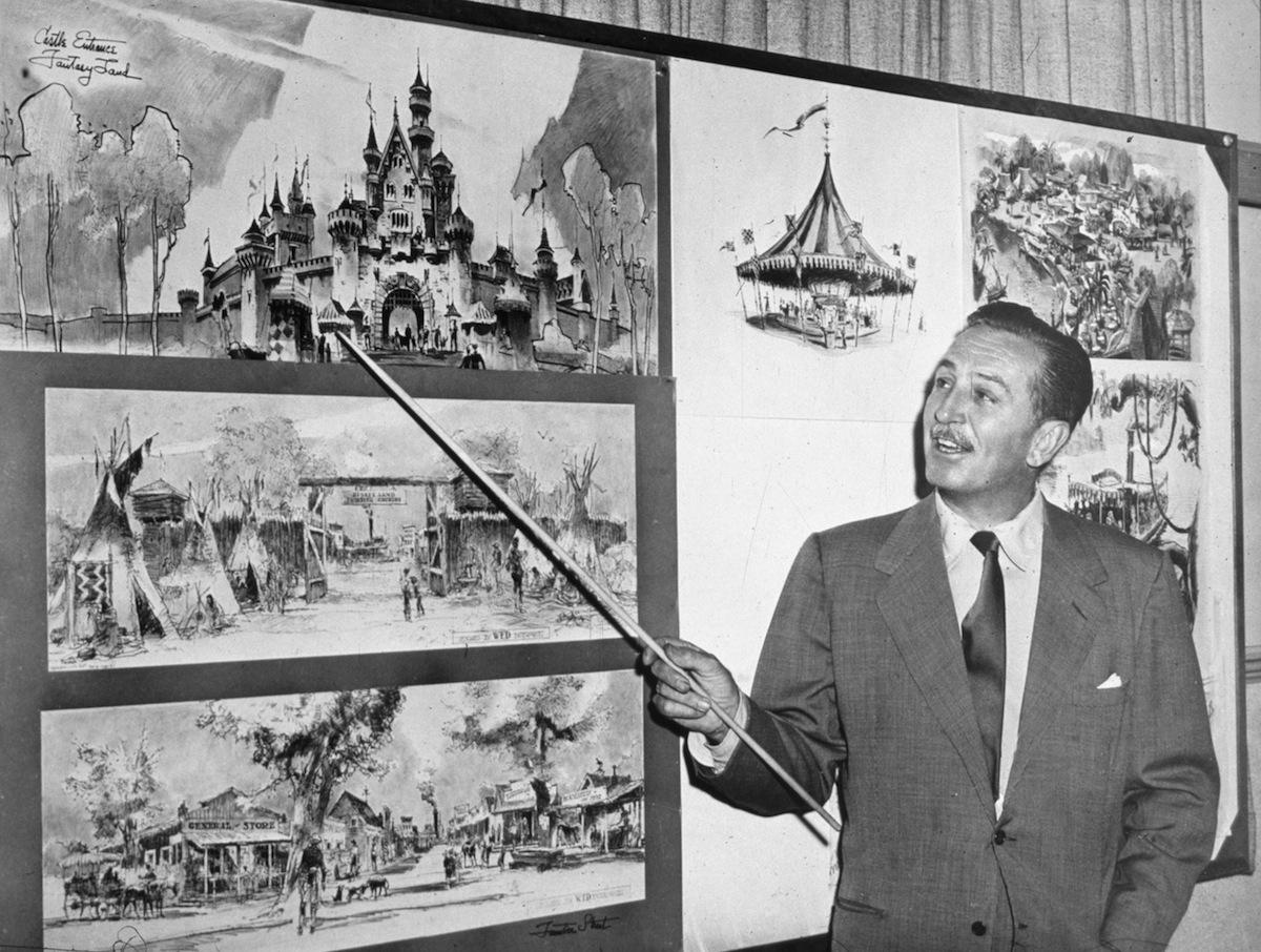 Walt Disney uses a baton to point to sketches of Disneyland, 1955.