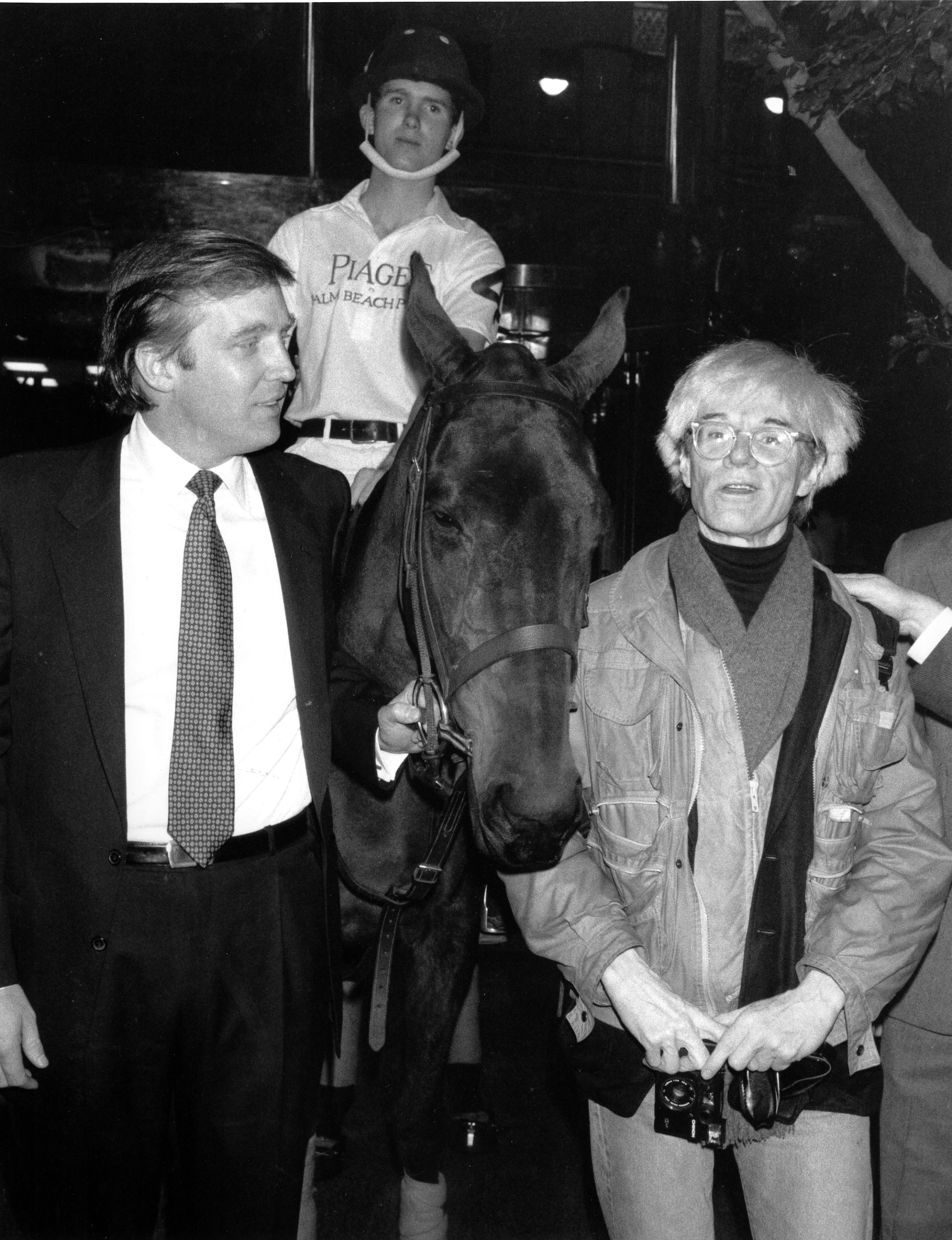 Donald Trump, owner of New York's Trump Tower, holds the bridle of a polo pony while talking to Andy Warhol on Nov. 4, 1983.