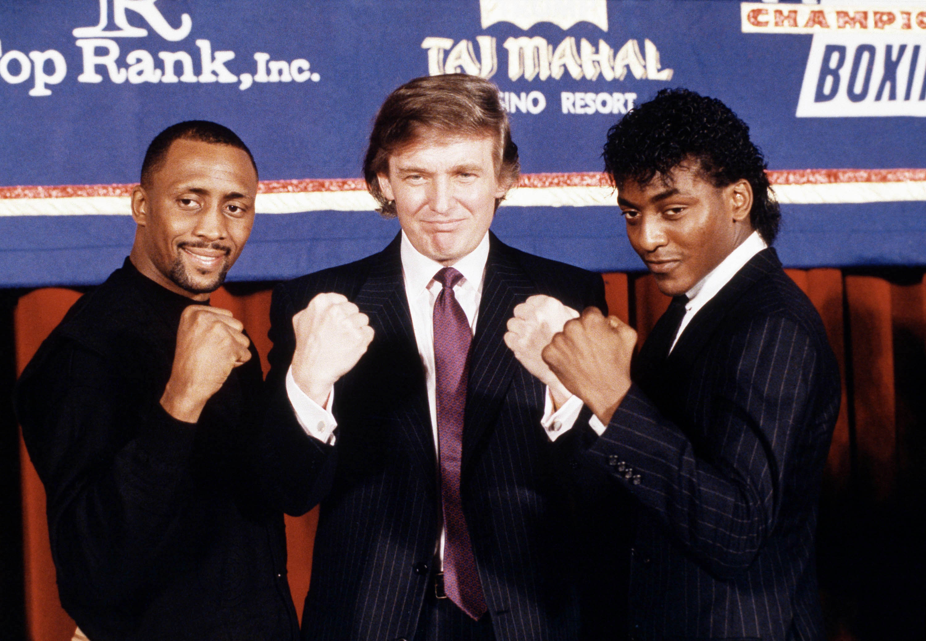 Developer Donald Trump is flanked by super middleweight champion Thomas Hearns, left, of Detroit, and Michael Olajide of Canada at a news conference in New York on Feb. 15, 1990.