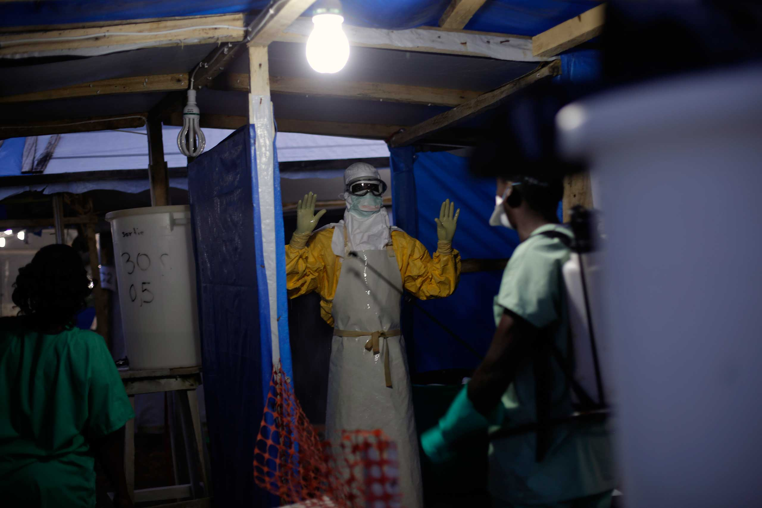 An MSF Ebola heath worker is sprayed as he leaves the contaminated zone at the Ebola treatment centre in Gueckedou, Guinea in Nov. 2014.