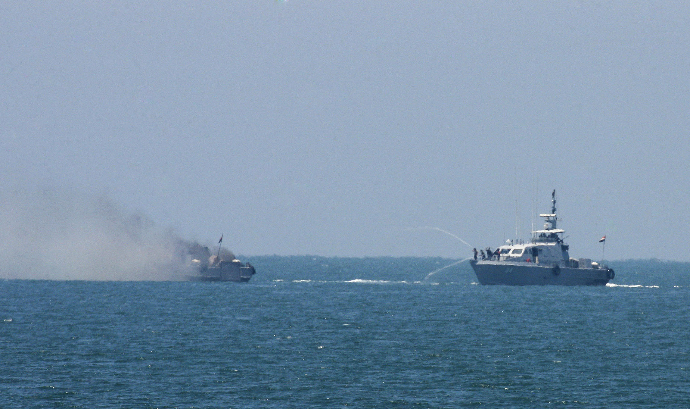 An Egyptian navy vessel hoses down another, which caught fire on the Mediterranean Sea after an exchange of gunshots with militants on July 16, 2015.