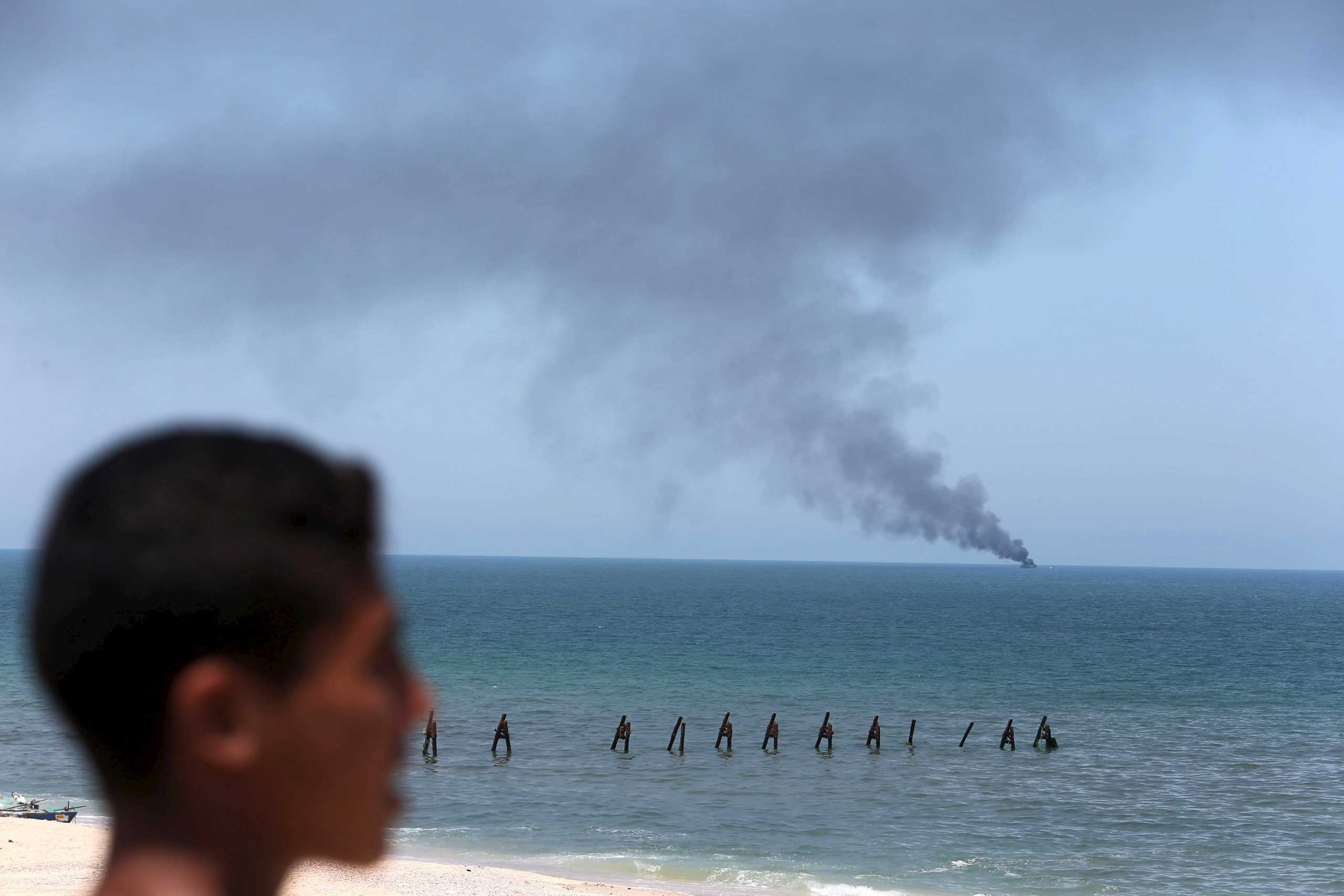 A Palestinian watches as smokes rises from an Egyptian coastguard vessel on the coast of northern Sinai, as seen from the border of southern Gaza Strip with Egypt, on July 16, 2015.