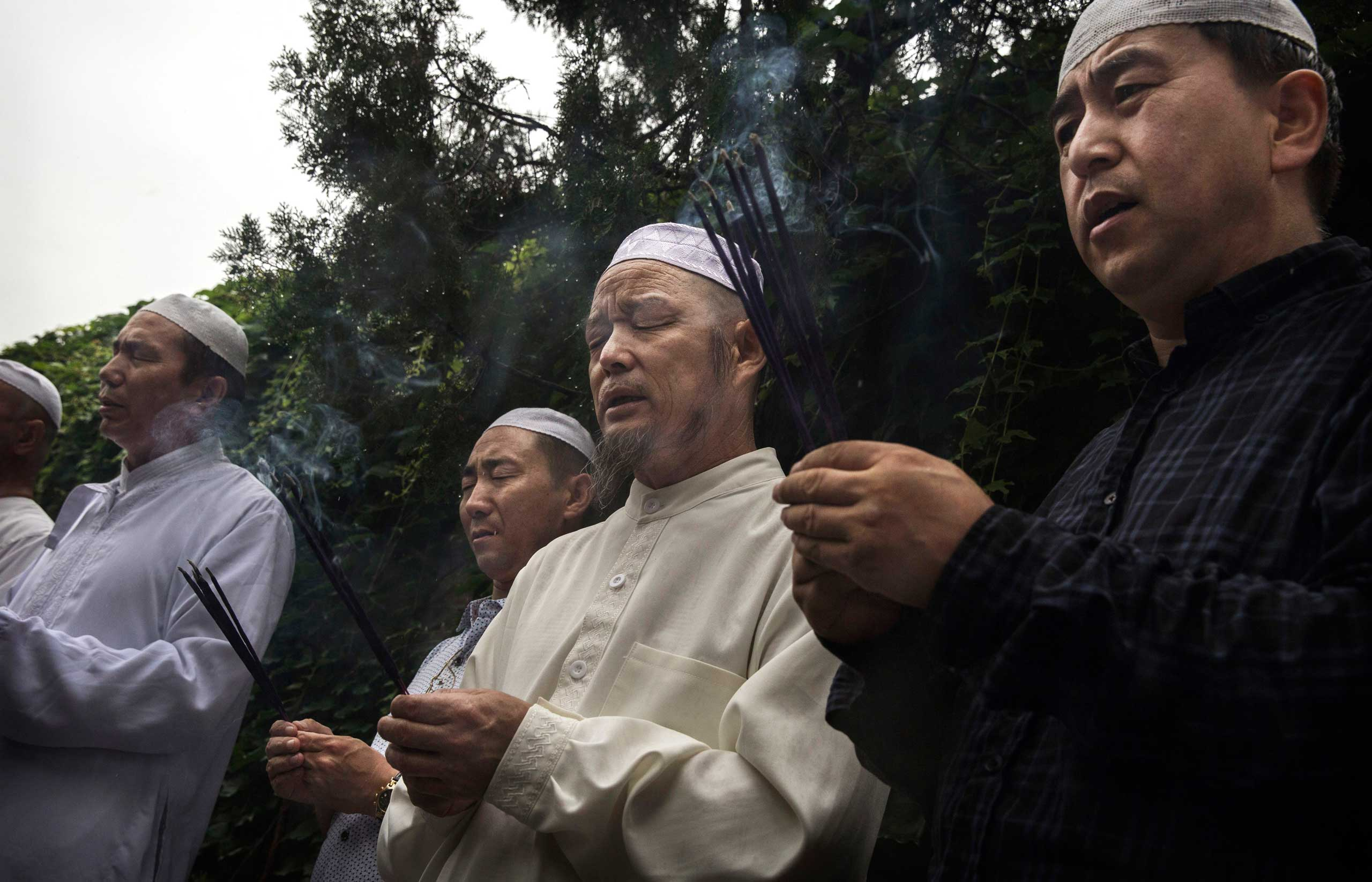 Chinese Muslims of the Hui ethnic minority hold incense as they pray at the Imam's Tomb before the last Friday prayers of the holy fasting month of Ramadan at the historic Niujie Mosque on July 17, 2015 in Beijing.