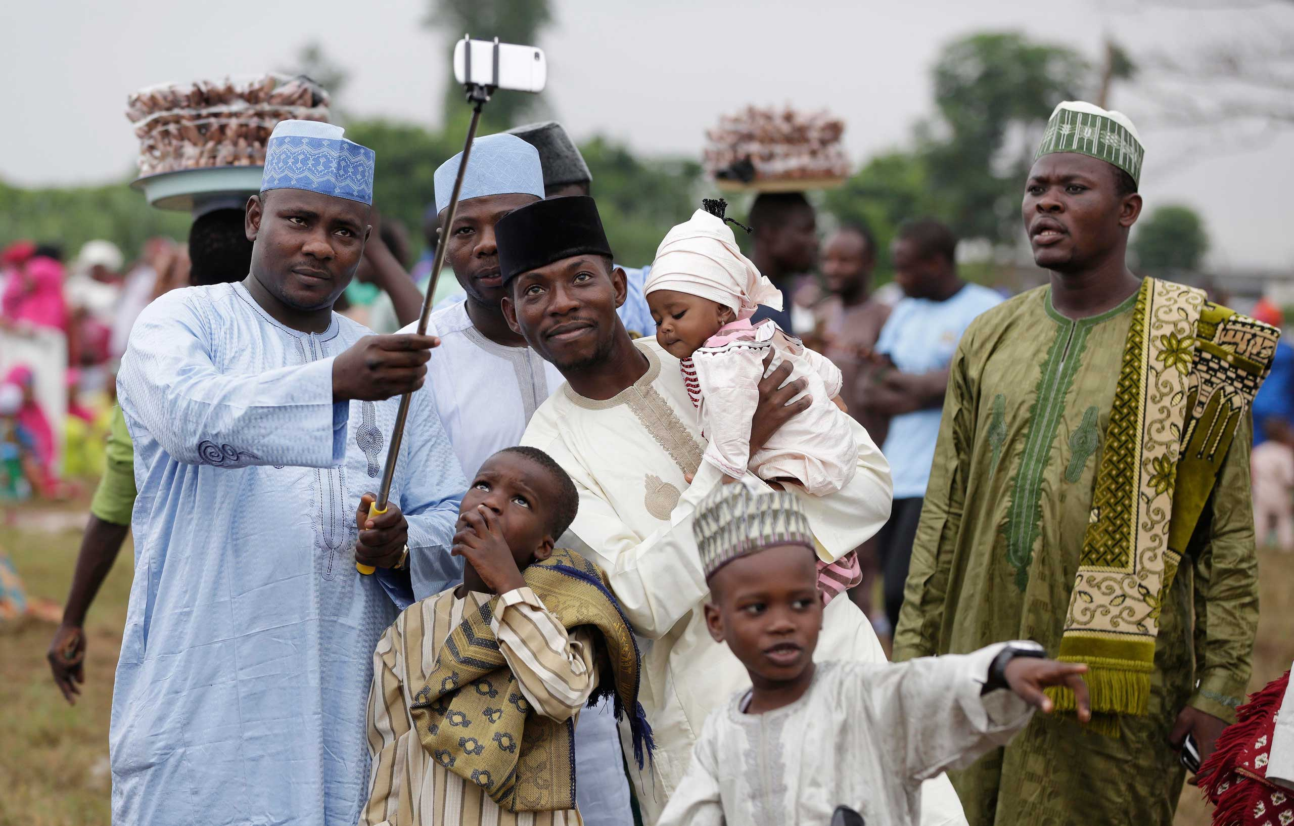 A Nigerian Muslim family takes a selfie portrait before Eid al-Fitr prayer, marking the end of the Muslim holy fasting month of Ramadan in Lagos, Nigeria, on  July 17, 2015.
