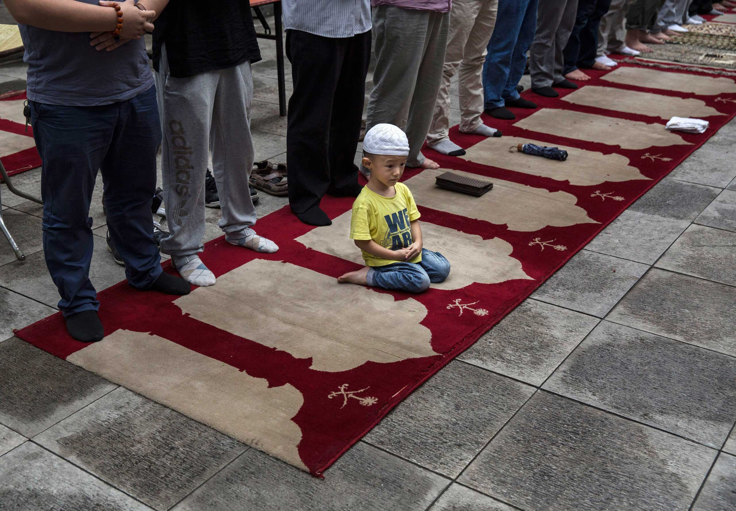 A young Chinese Muslim of the Hui ethnic minority sits on a prayer rug as men stand and pray during the last Friday prayers of the holy fasting month of Ramadan at the historic Niujie Mosque on July 17, 2015 in Beijing.