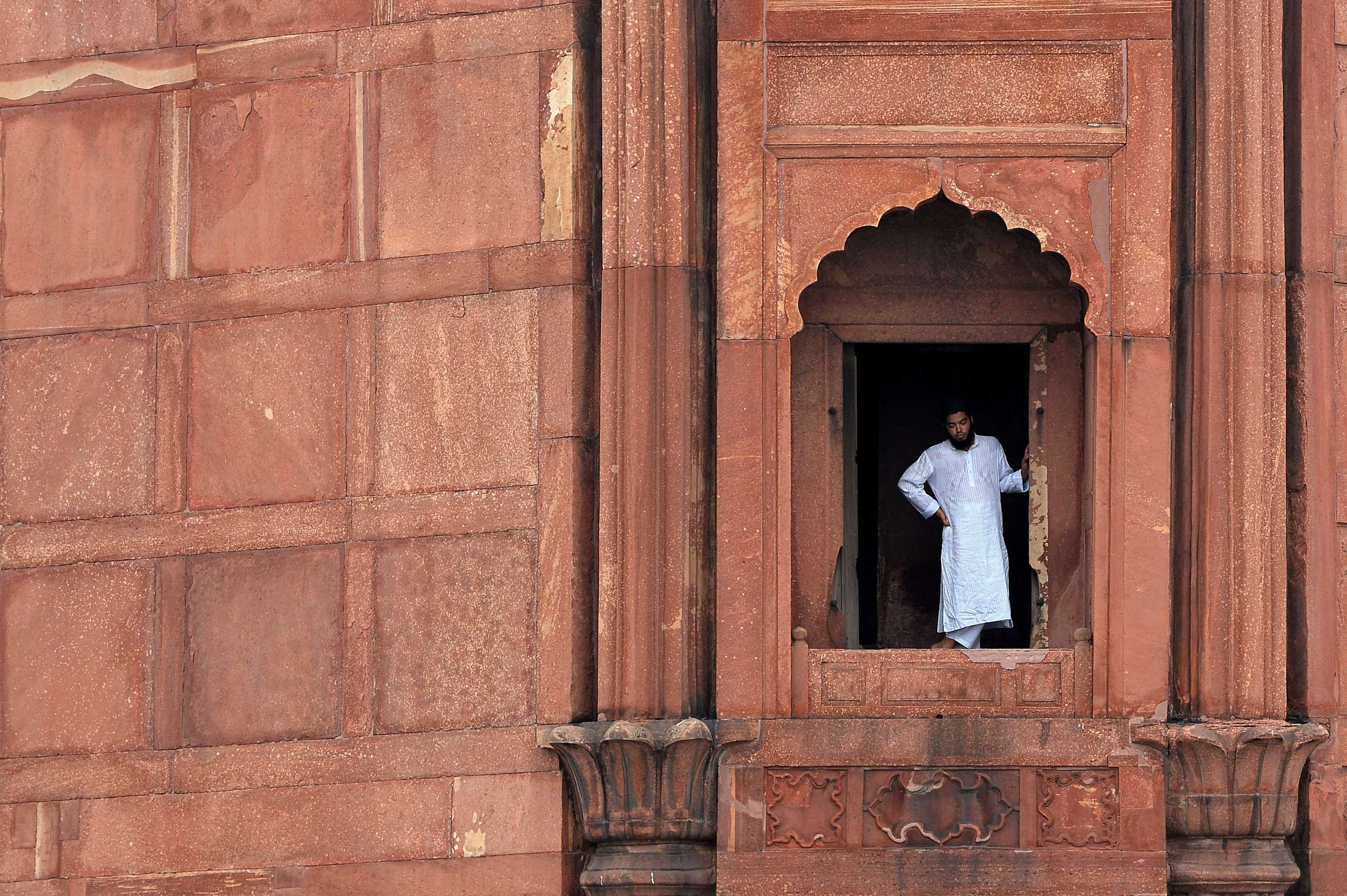 An Indian Muslim devotee looks on before the start of Jummat-Ul-Vida prayers on the last Friday of the month of Ramadan ahead of the Eid al-Fitr holiday at Jama Masjid Mosque in the old quarters of New Delhi on July 17, 2015.