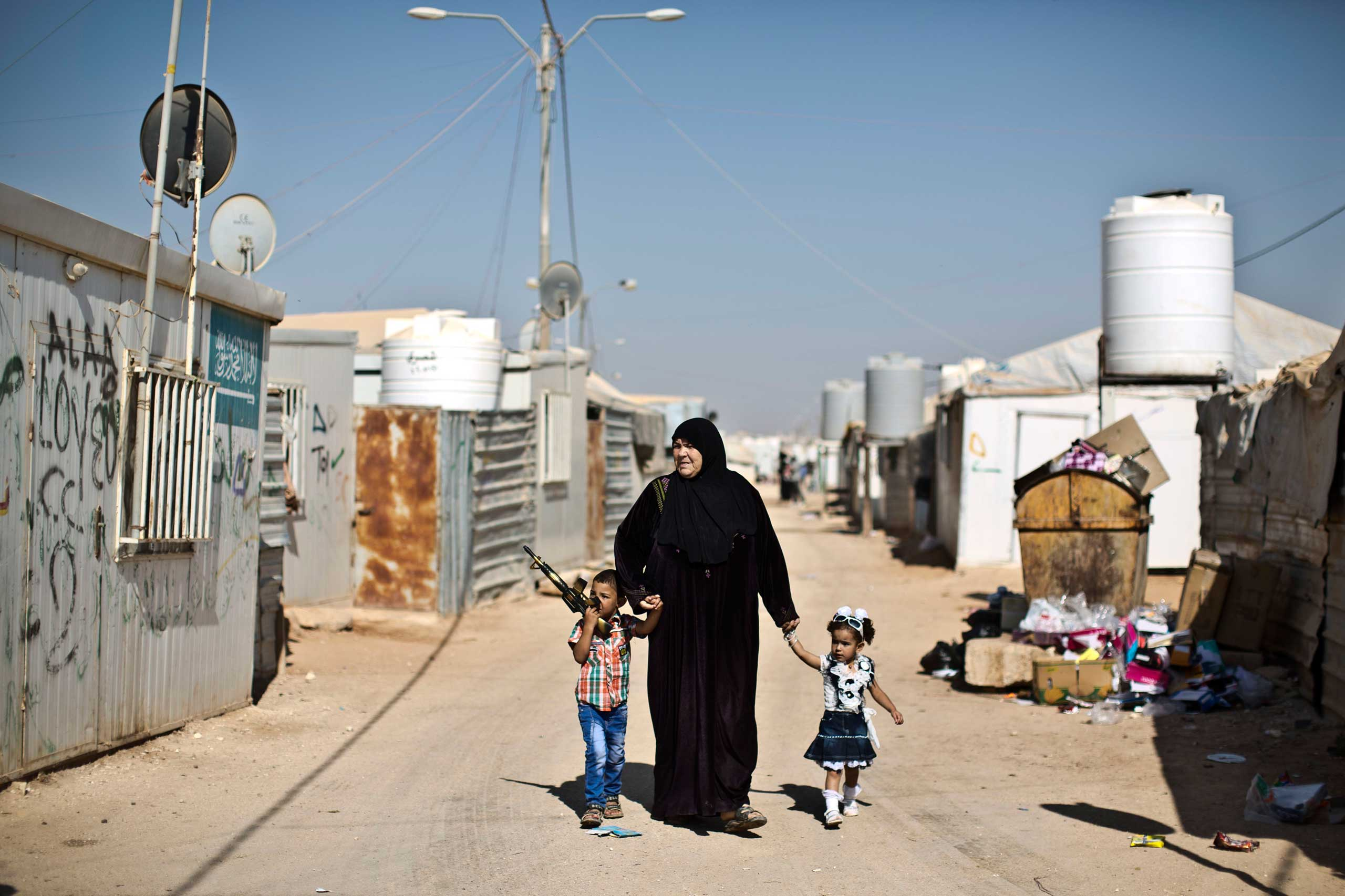 Syrian refugee children dressed in new clothes hold the hands of their grandmother while walking back to their shelter on the first day of the Eid al-Fitr holiday that marks the end of the holy fasting month of Ramadan at Zaatari refugee camp, in Mafraq, Jordan, on July 17, 2015.