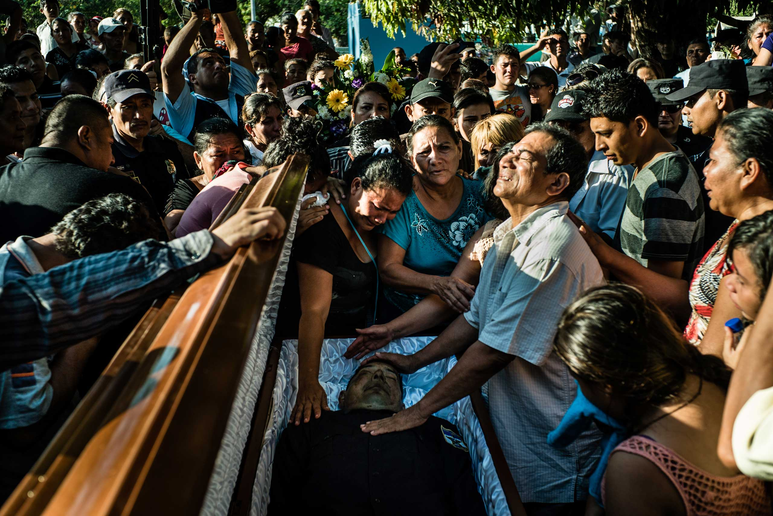 Parents and the wife of a murdered police officer mourn his death at his funeral, in Herradura, on March 16, 2015.