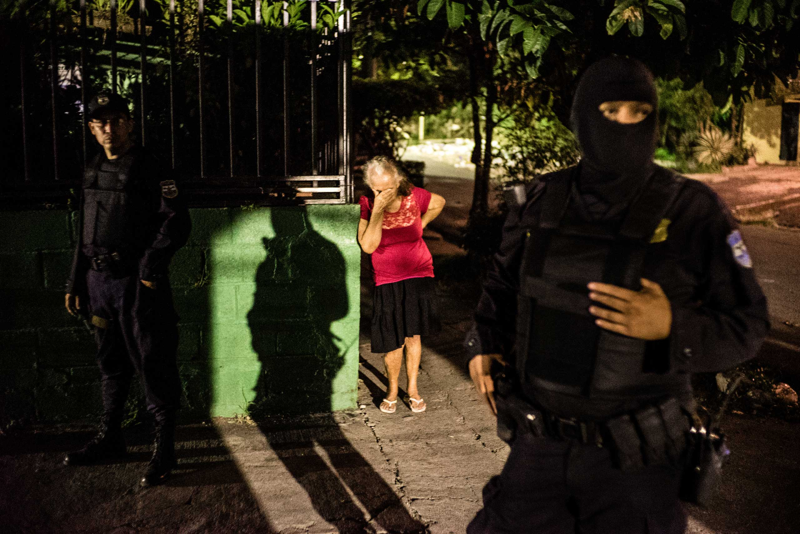 An older woman cries in the district of Soyapango while police conducts a night raid in search of Mara Salvatrucha gang (MS 13) members, San Salvador, on June 11, 2015.